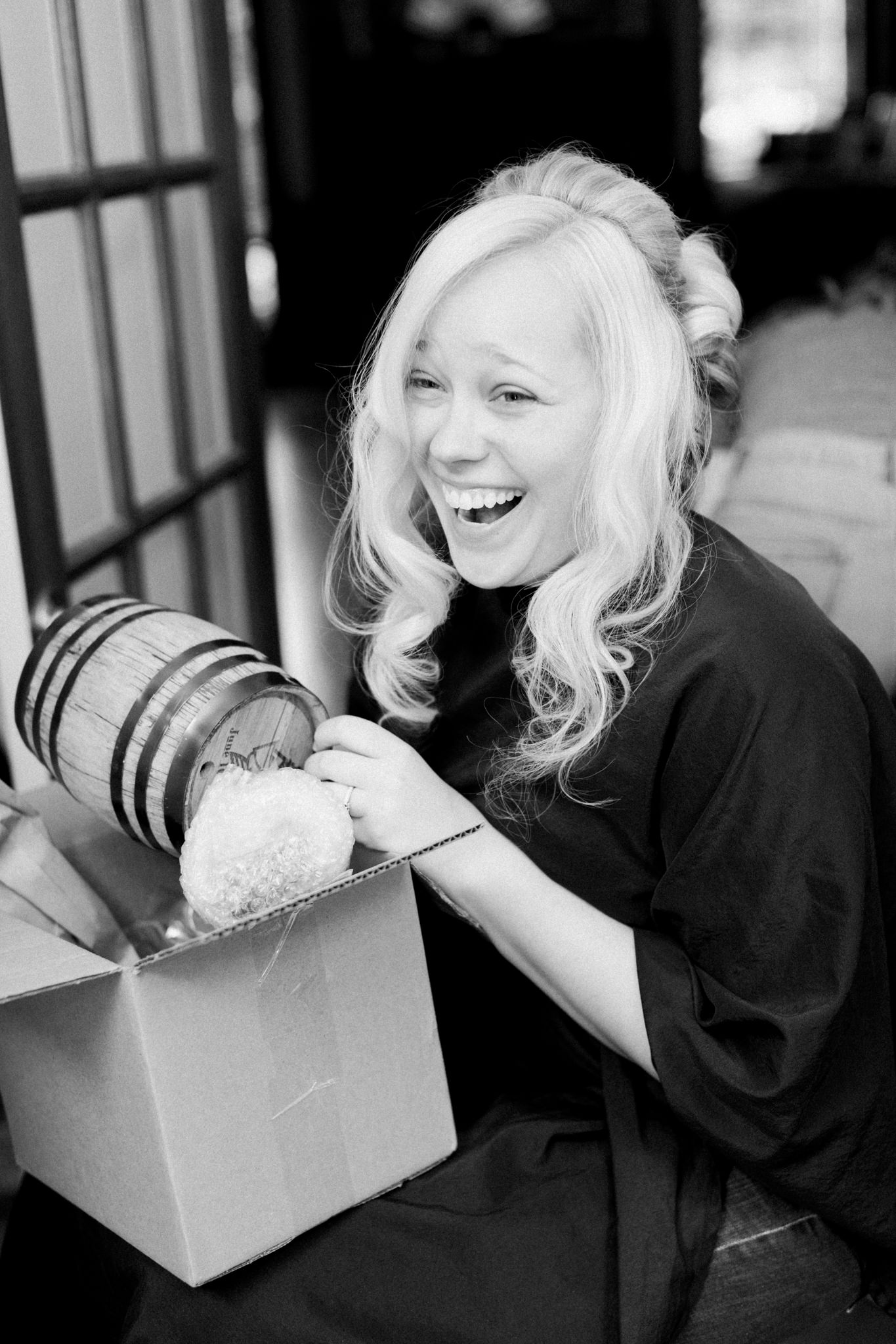 Bride laughing as she opens up her small bourbon barrel gift from the groom on her wedding day.