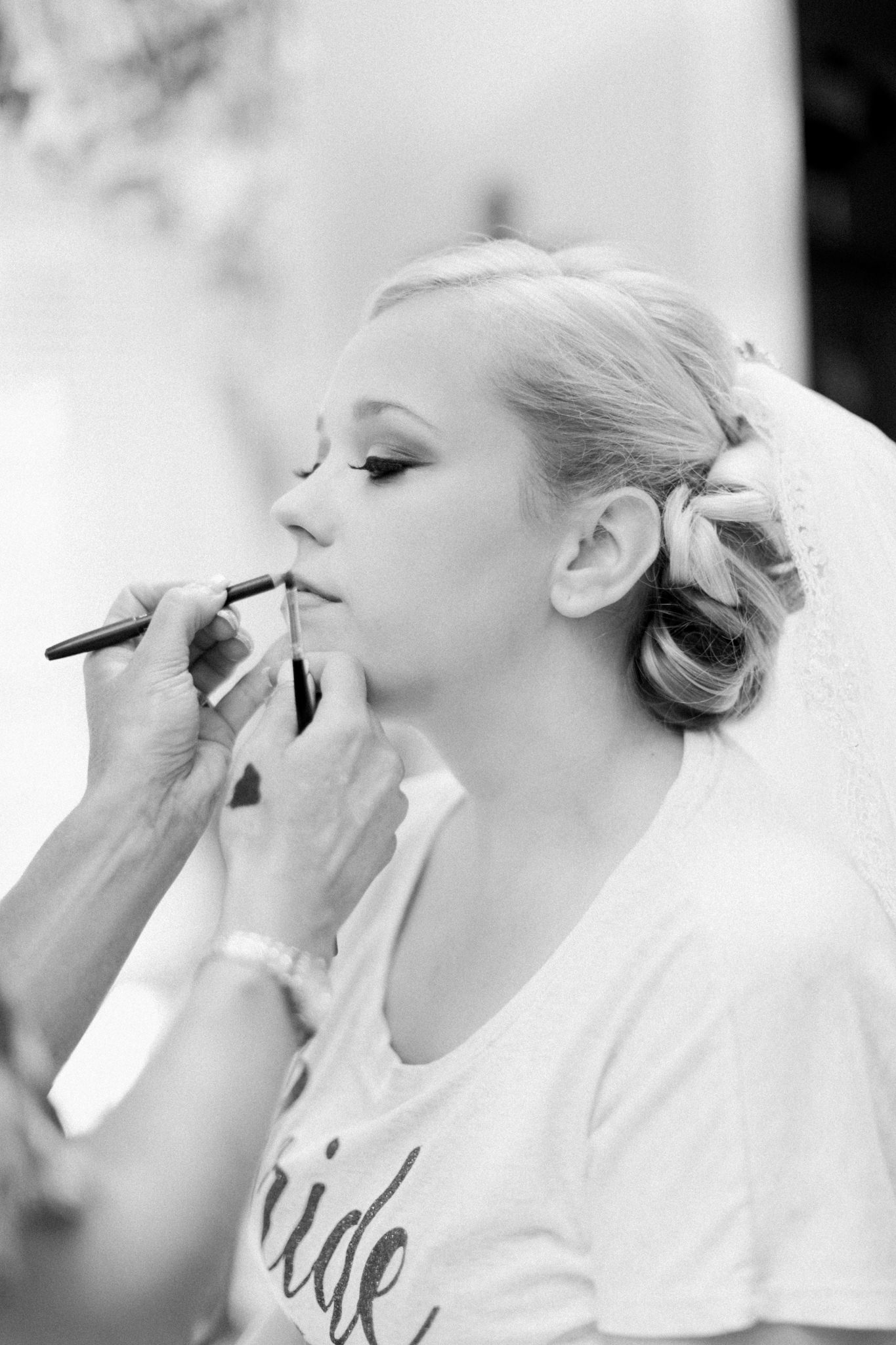 Bride getting lipstick applied by her makeup artist before her Louisville wedding at St. Agnes Catholic Church.