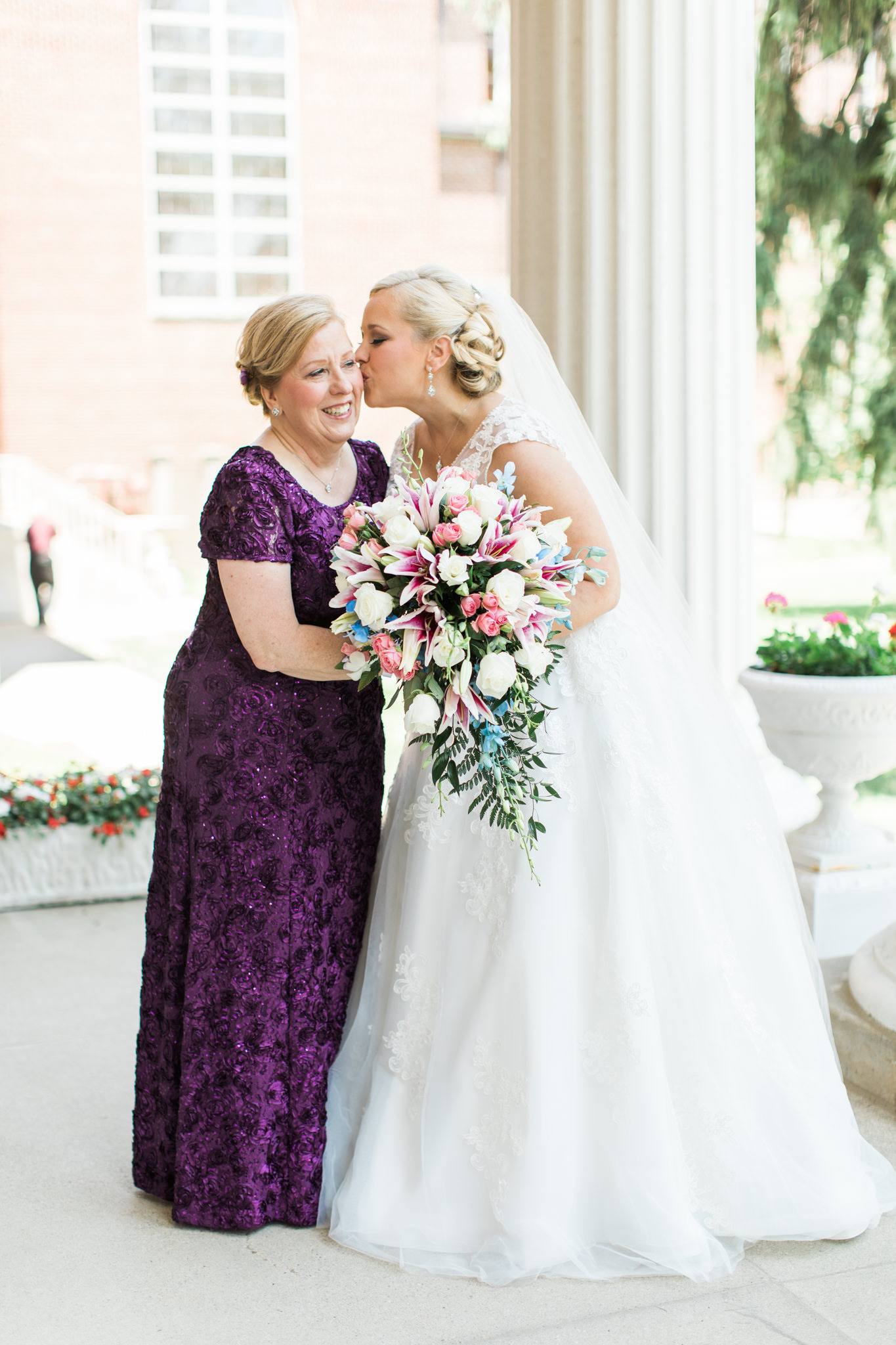 Bride kissing her mother on the cheek at St. Agnes Catholic Church for Louisville Ky wedding.