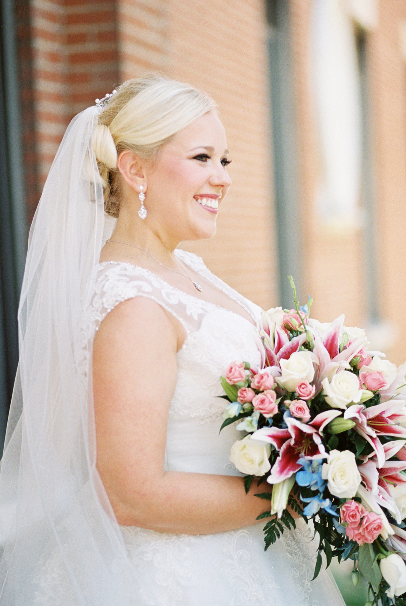 bride holding teardrop shaped cascading bouquet at st. agnes wedding in louisville ky
