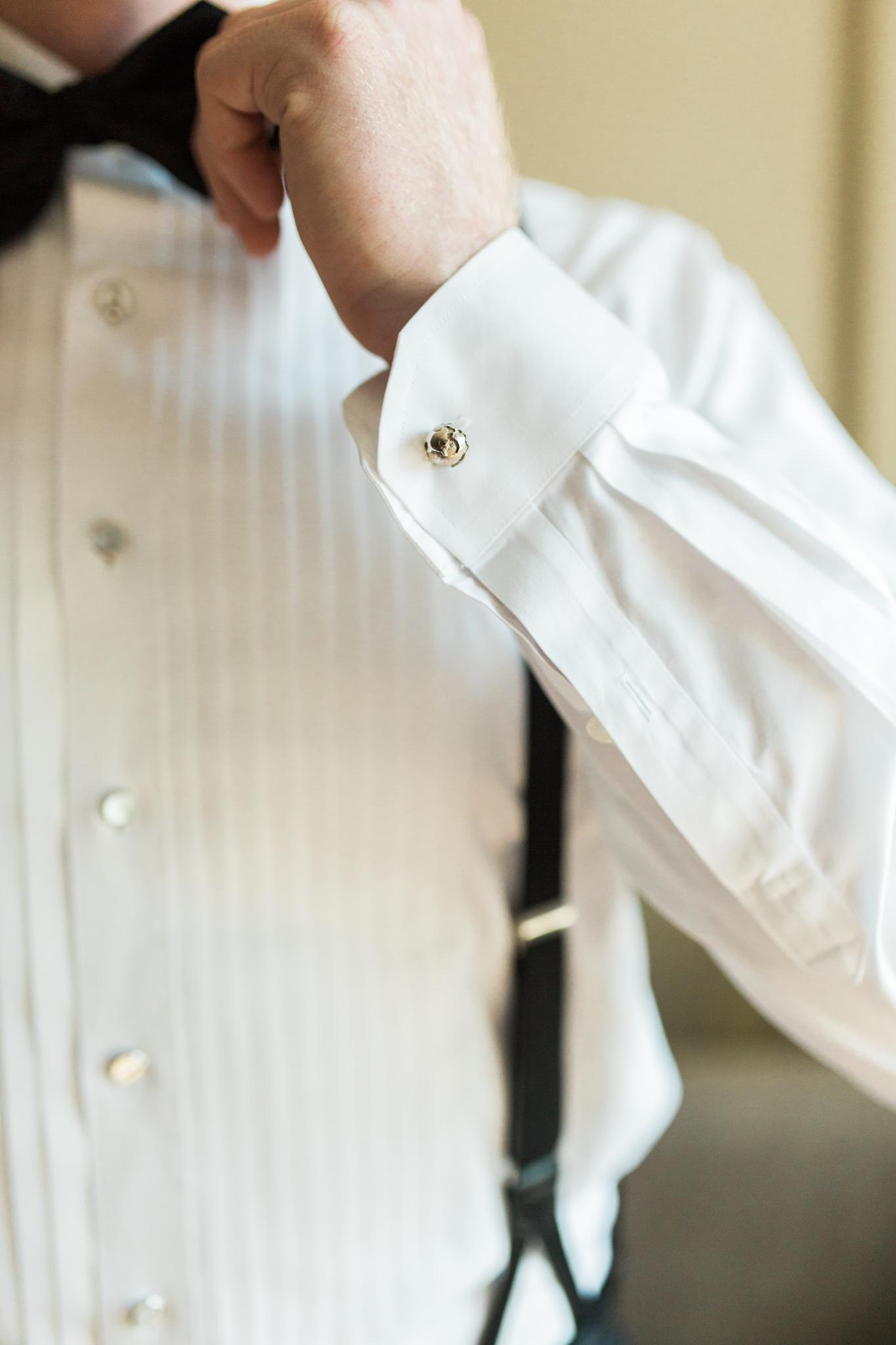 Groom adjusting his bowtie before his wedding