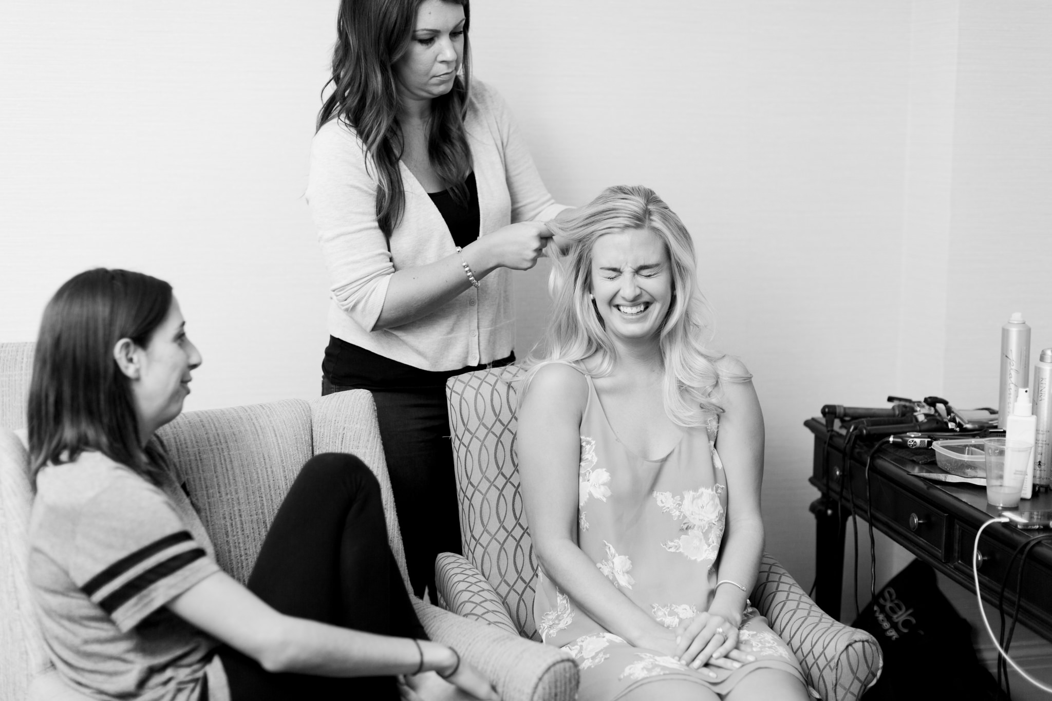 Bride laughing while getting her hair done black and white photo