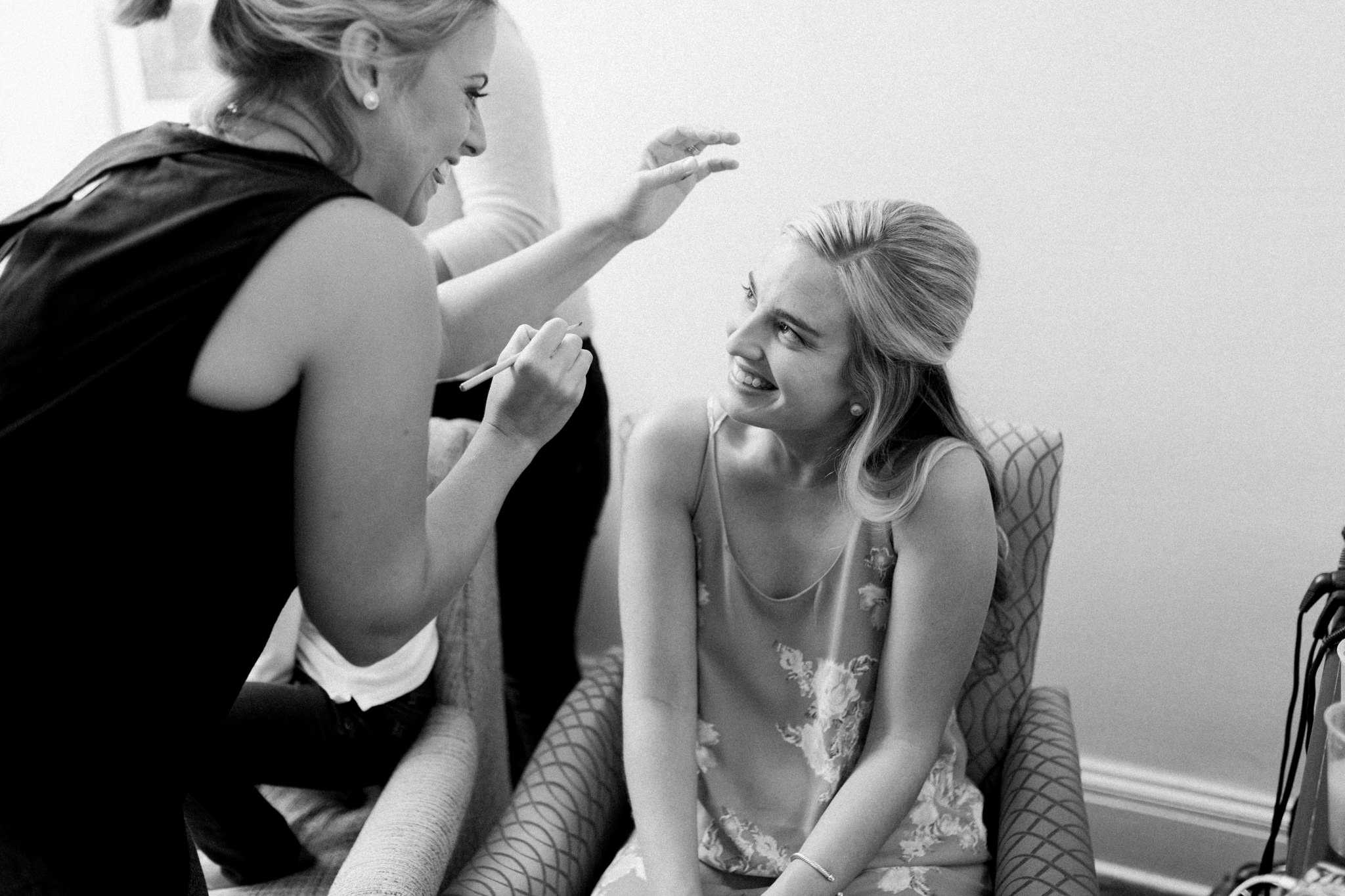 Black and white photo of bride and makeup artist laughing