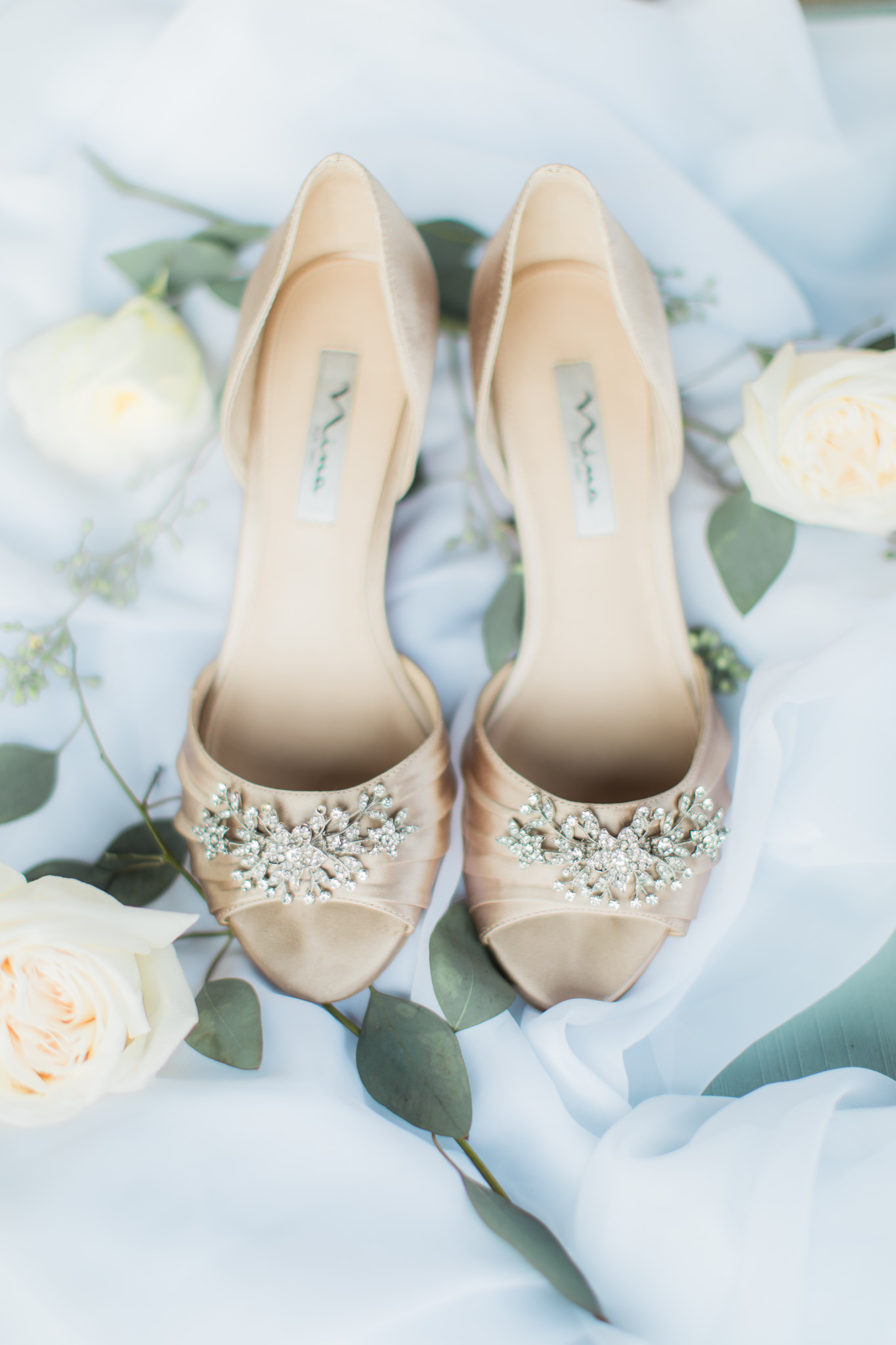 flat lay of nina champagne wedding shoes and euchalyptus greenery and cream garden roses