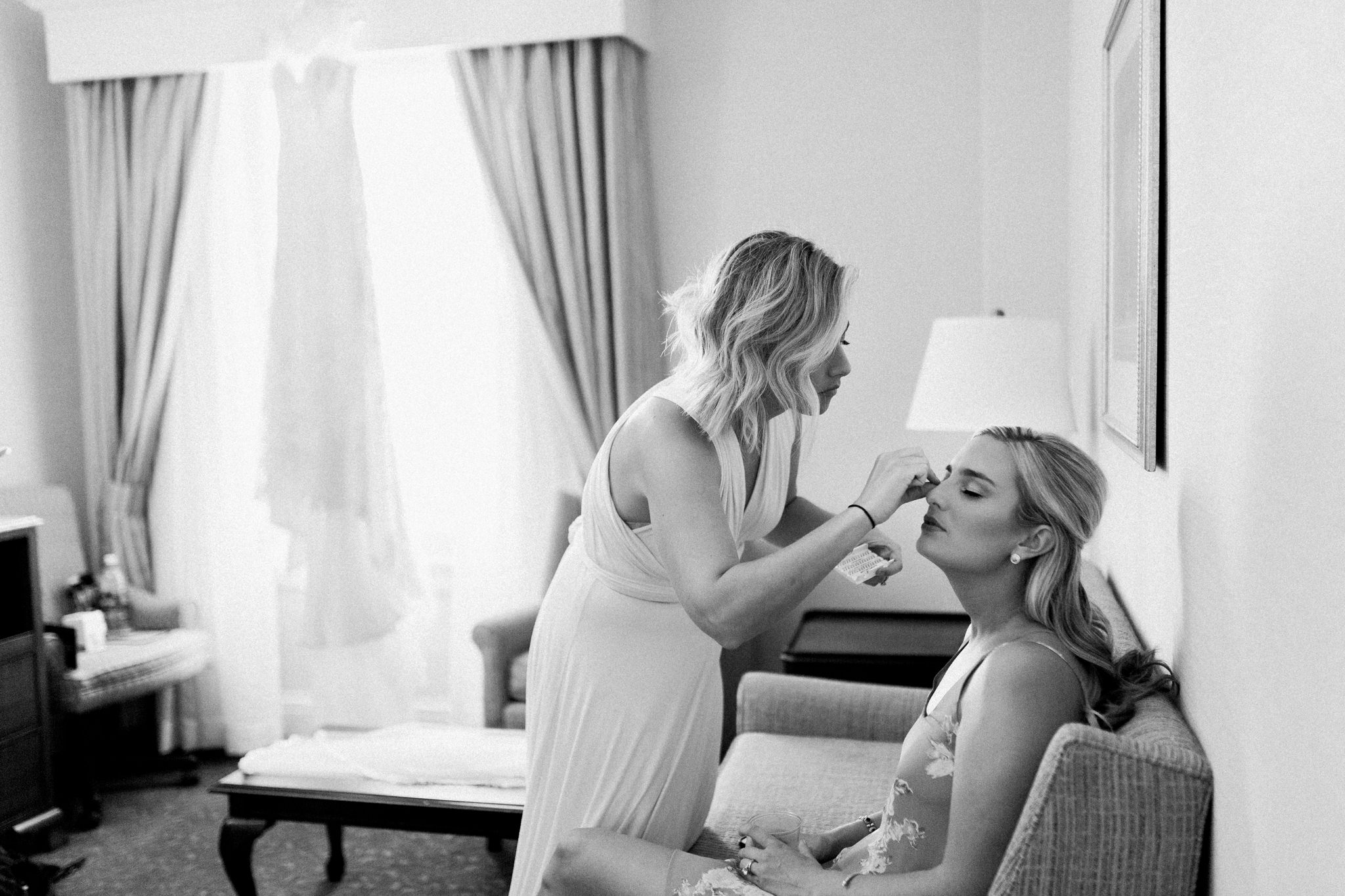 Bride getting makeup done in a hotel room with her dress hanging in the window