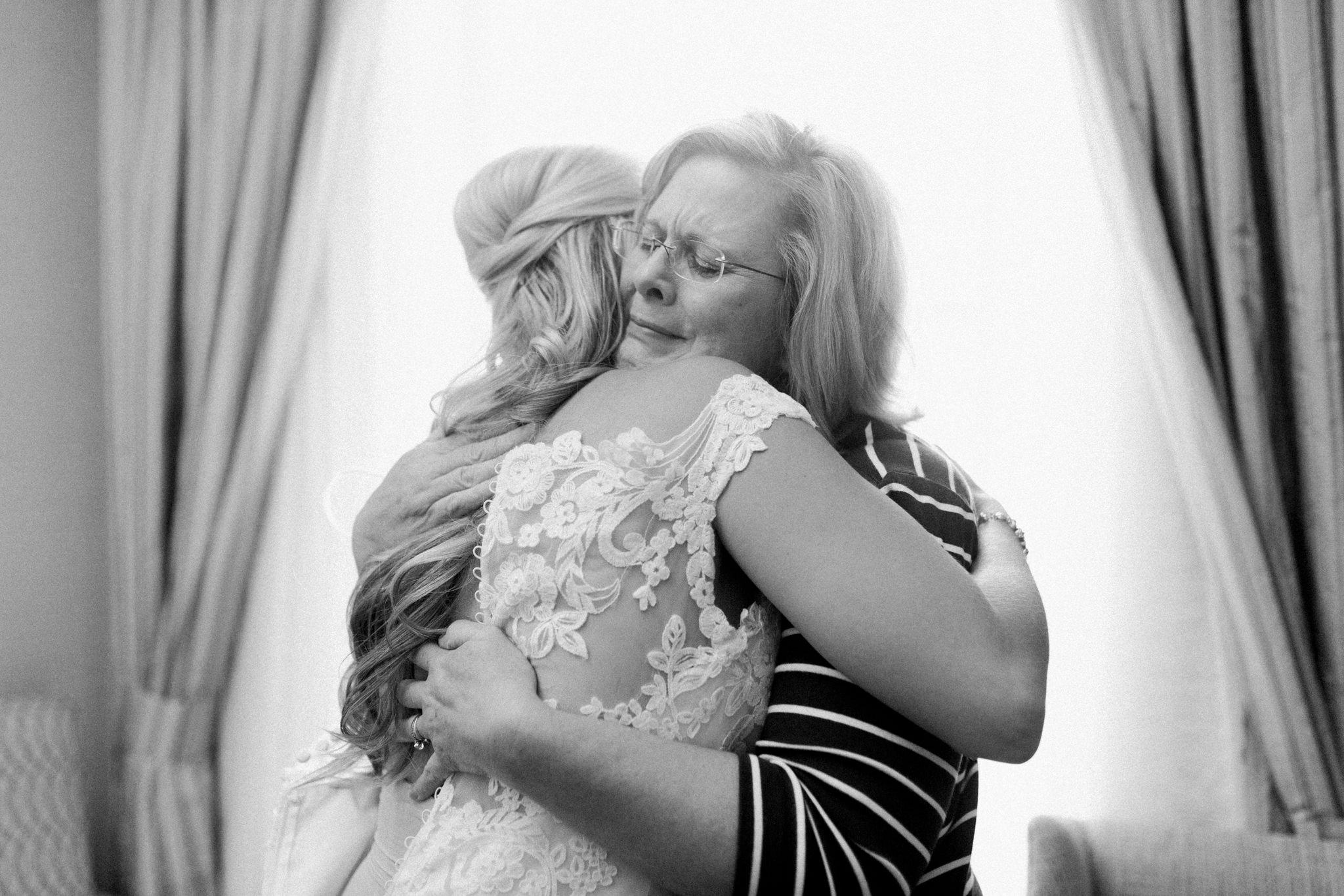 Bride and mother of the bride hugging sentimental
