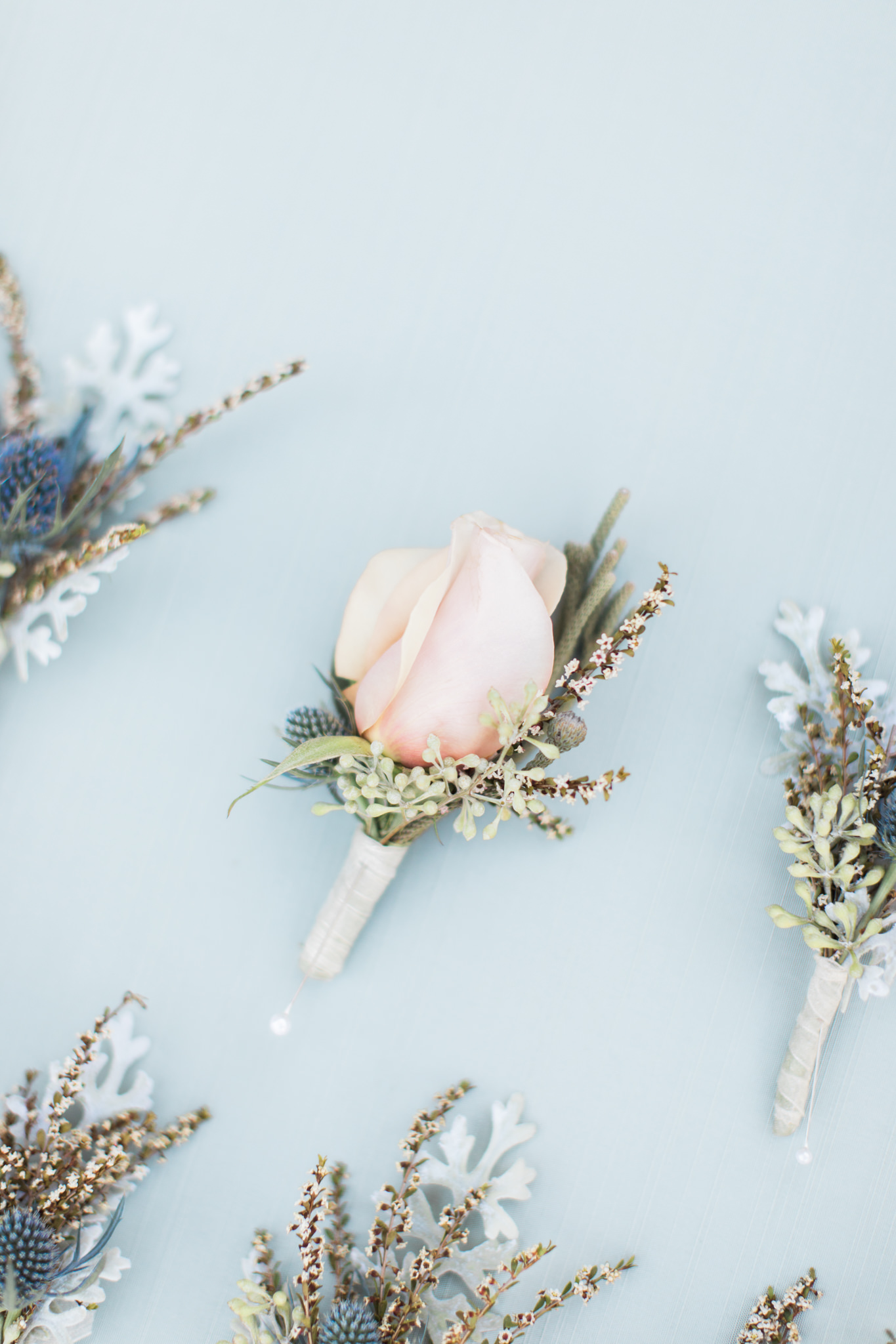 blush rose boutonnieres with greenery and white ribbon flat lay