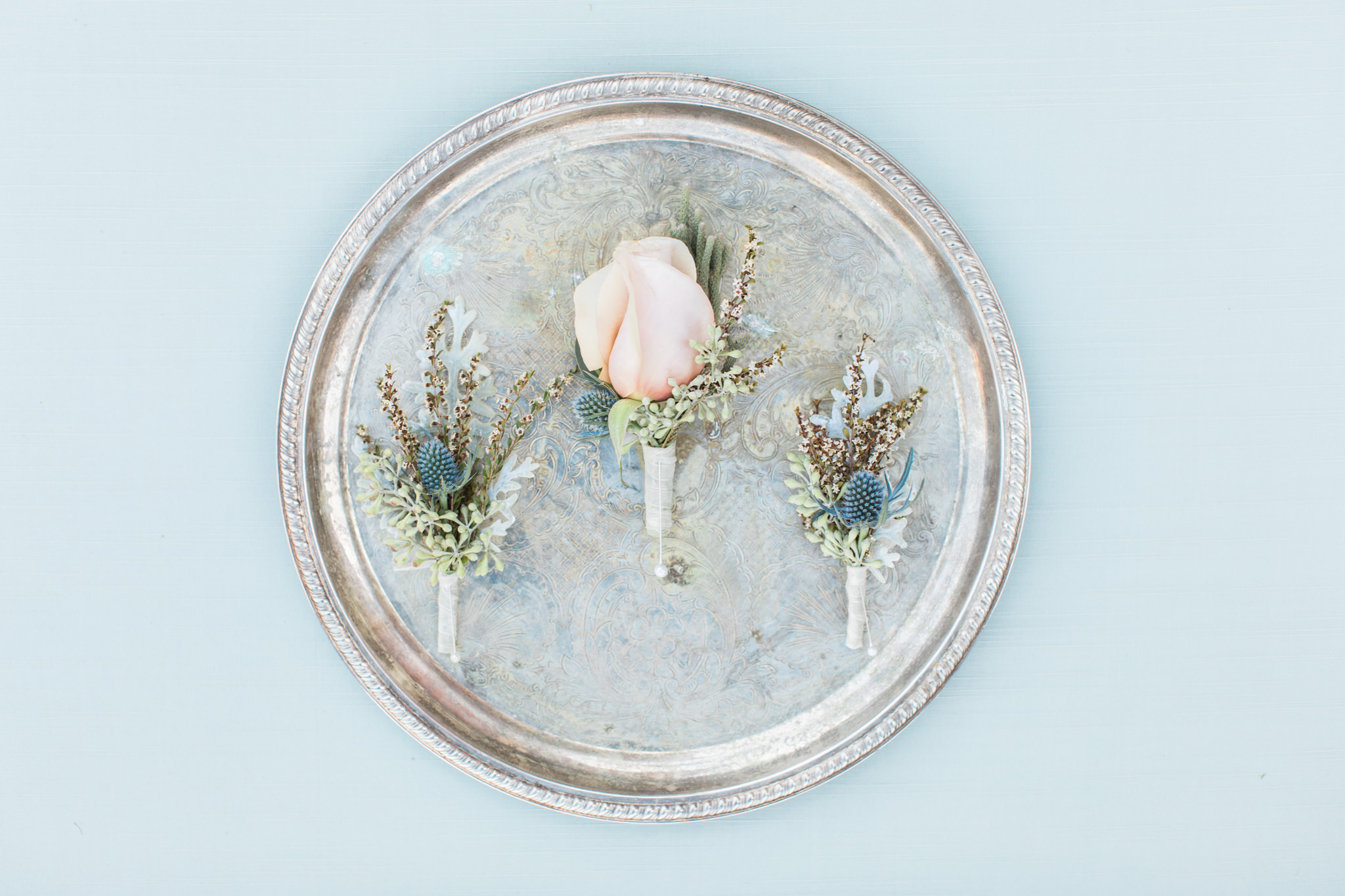 blush rose and greenery boutonnieres on a silver platter and styling board
