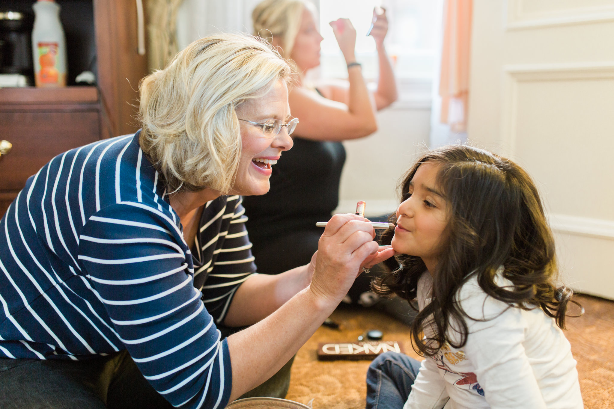 Mother of the bride putting lipstick on her daughter