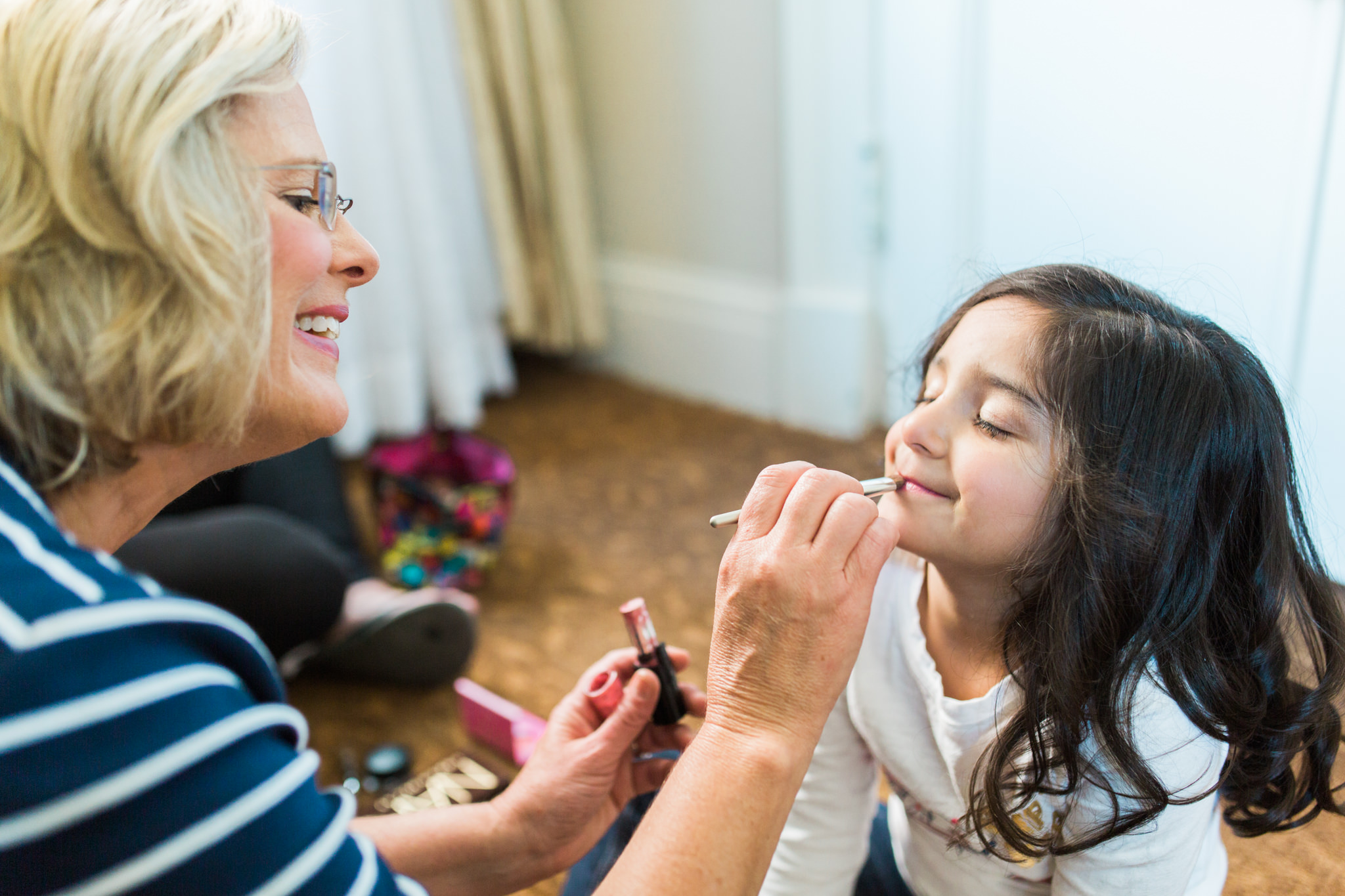 mother of the bride putting lipstick on her youngest daughter before the wedding