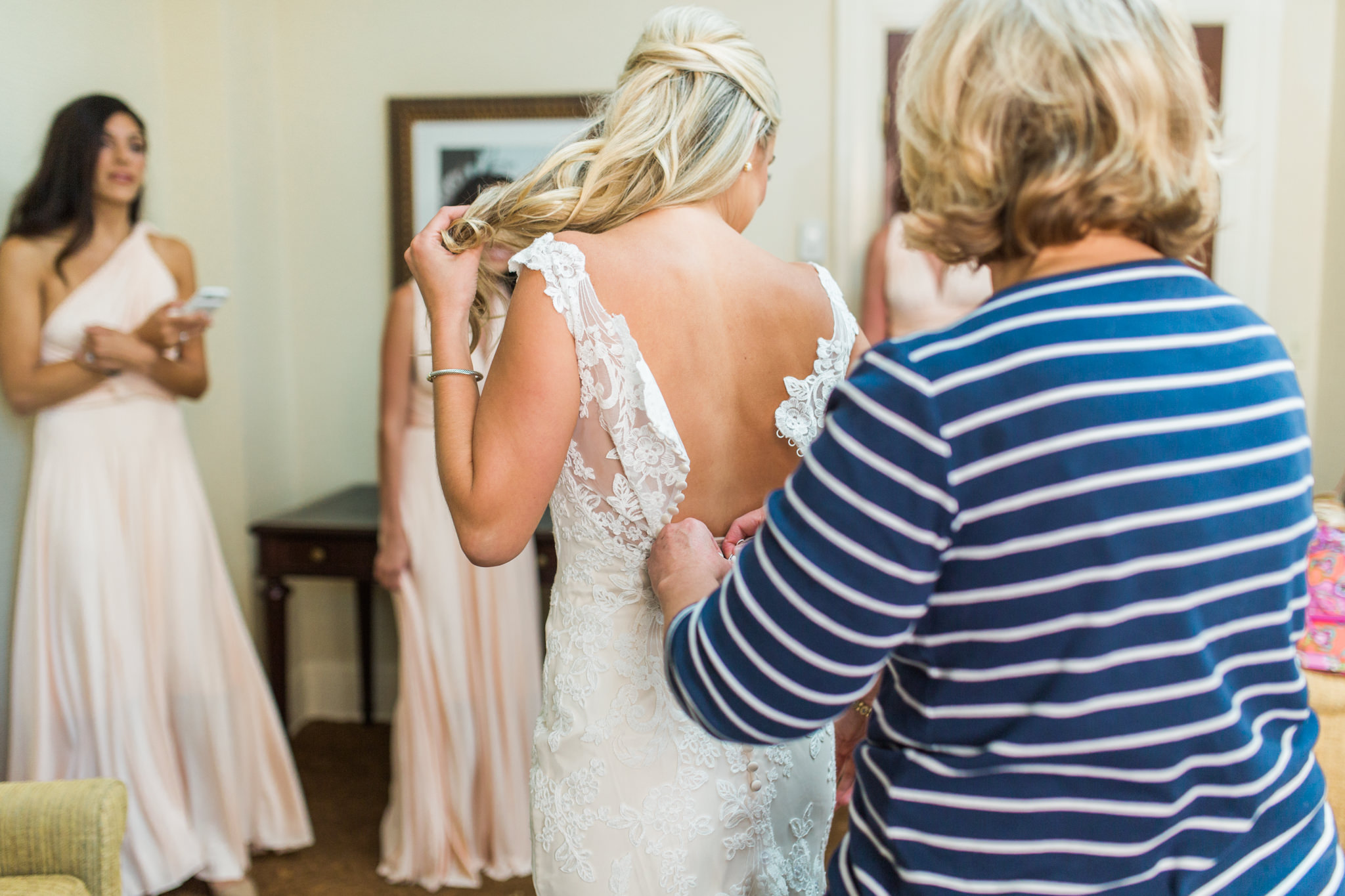 Mother of the bride buttoning her daughter's dress