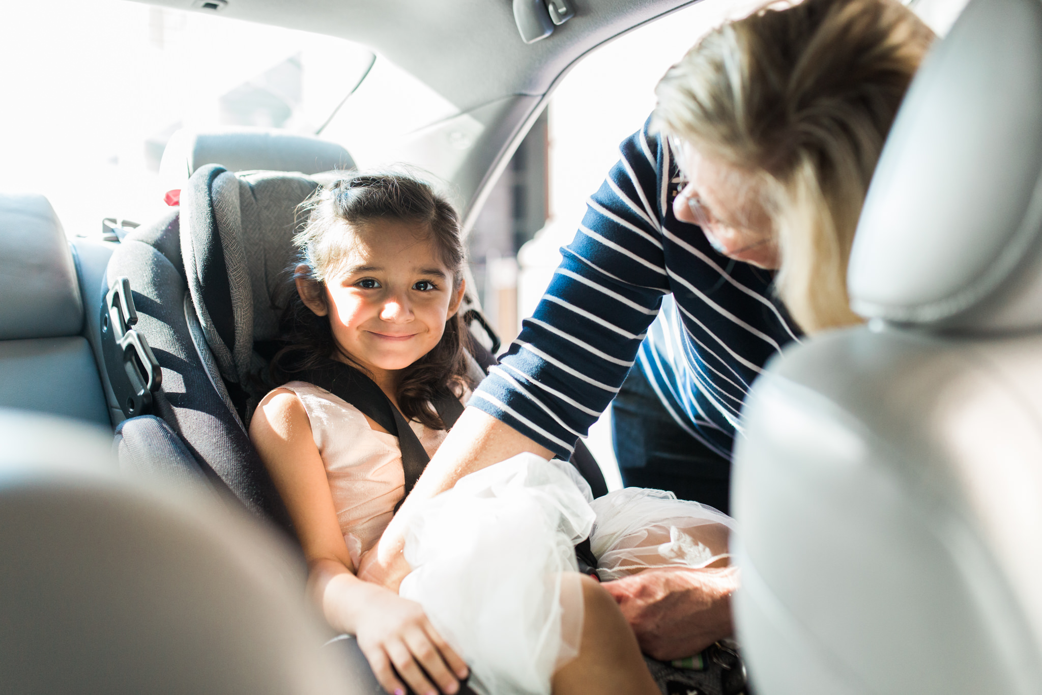 Mother of the bride buckling little girl in her car seat before the wedding