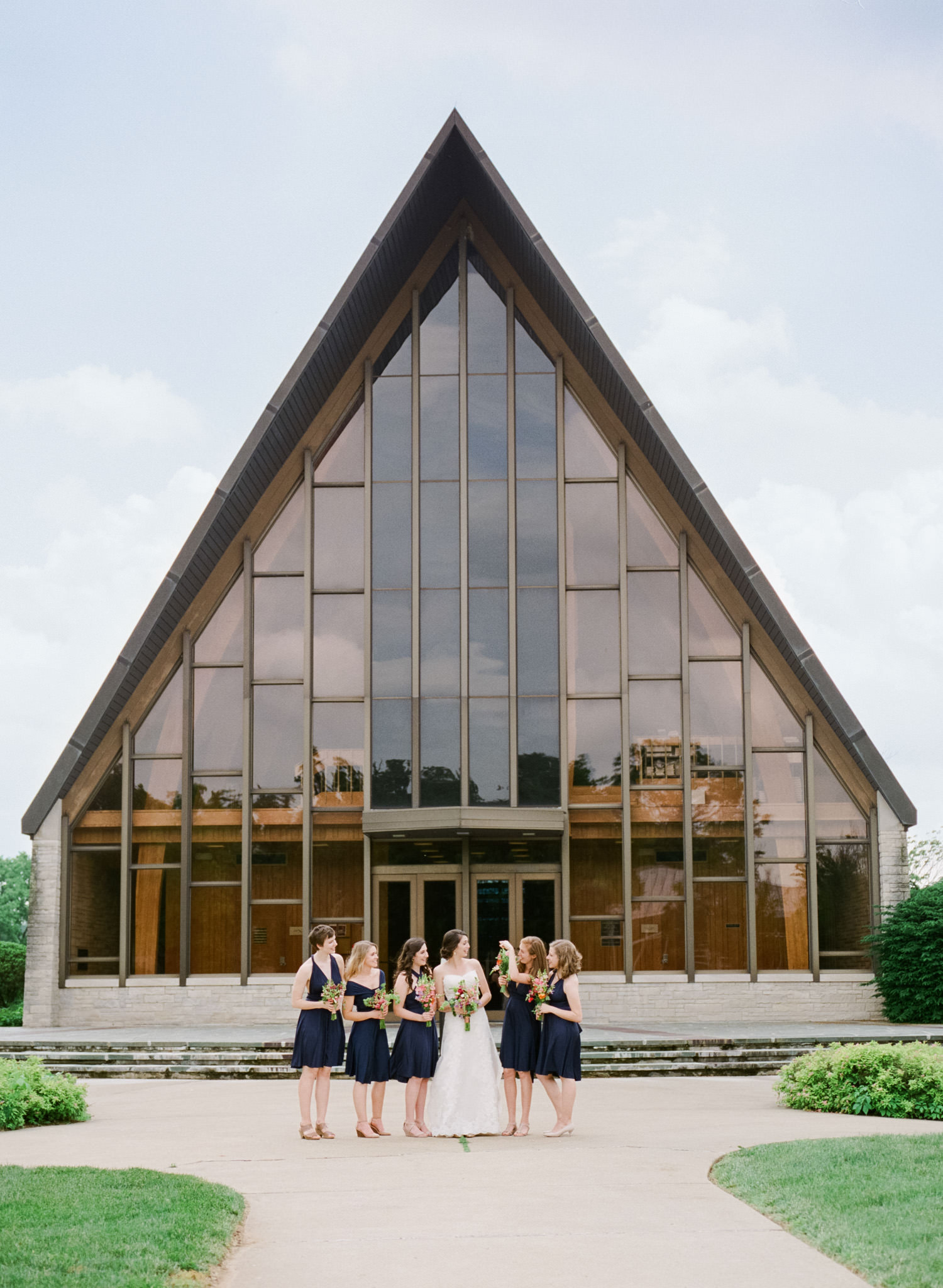 Photo of bridesmaids standing outside during a Louisville wedding at Caldwell Chapel Gardencourt on a summer day in Louisville Ky