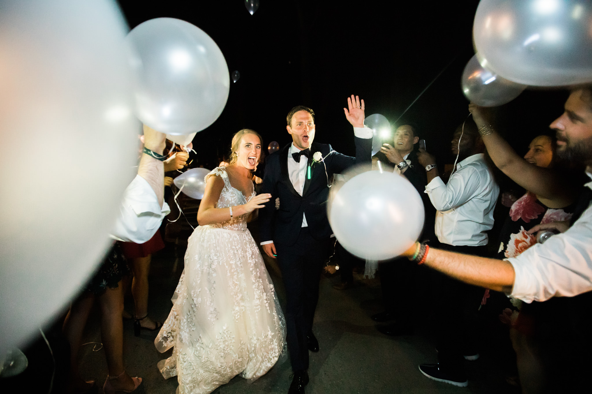 low light wedding photography example of couple outside during LED balloons