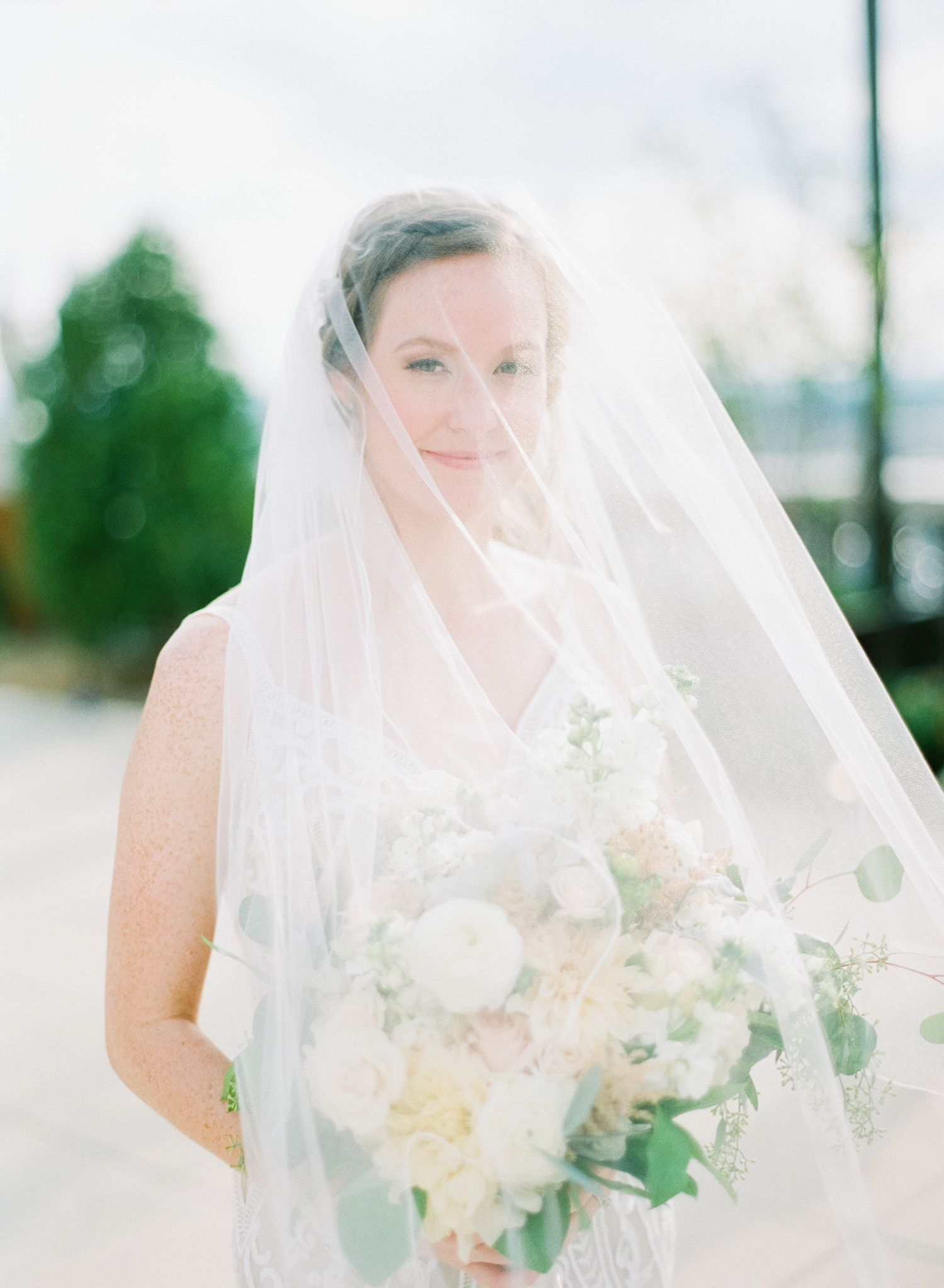 Ethereal portrait of bride with veil holding bouquet