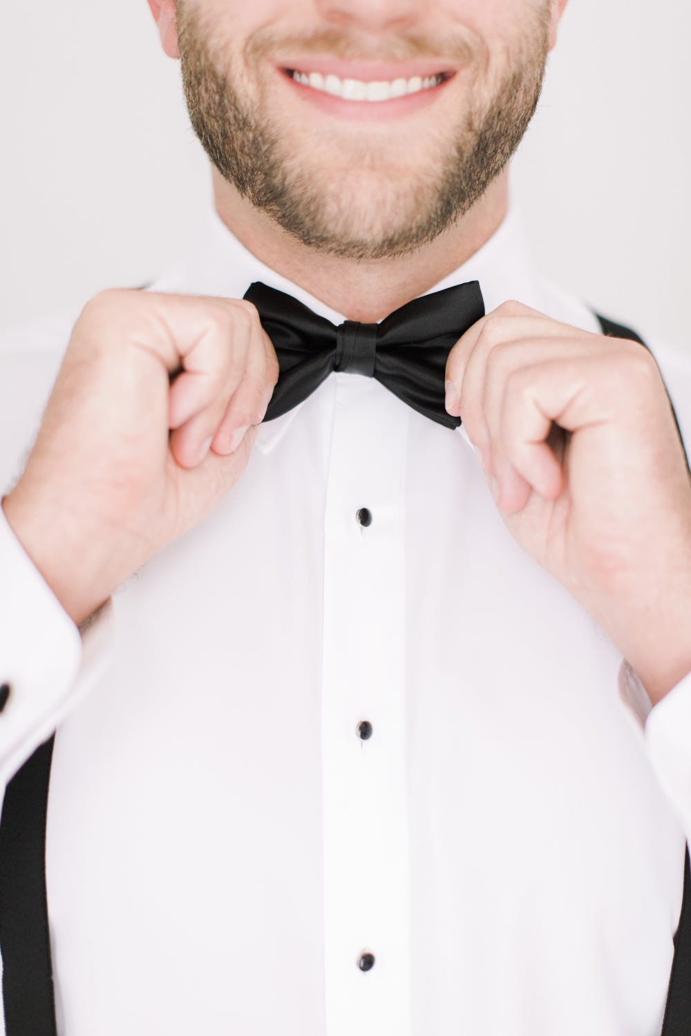 Well-dressed groom adjusting his black bow-tie