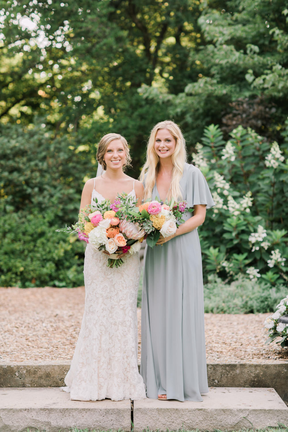 Yew Dell Wedding Photo of Bride and Maid of Honor holding bouquets in botanical garden