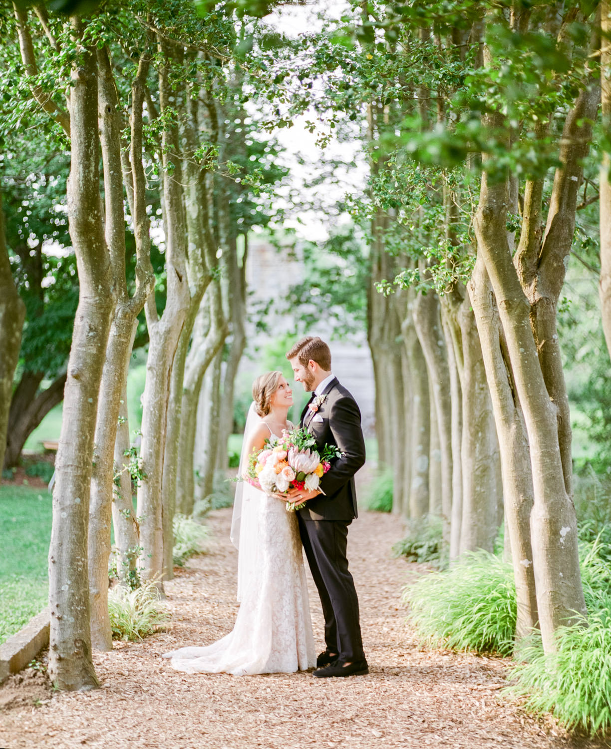 Yew Dell Wedding Photo of bride and groom holding bouquet in between unique trees, taken by Louisville Wedding Photographers Jeff & Michele