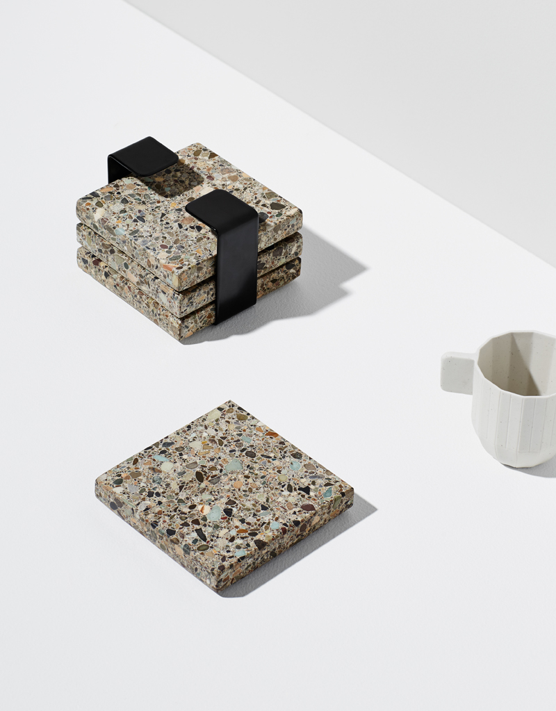 Habitat Set - Habitat is a 4-piece trivet set, made from natural, earthy Terrazzo stone. Finished with a steel band to house them when not in use. They make a textural addition to any tabletop. Use them as individual coasters or piece together for a larger trivet.