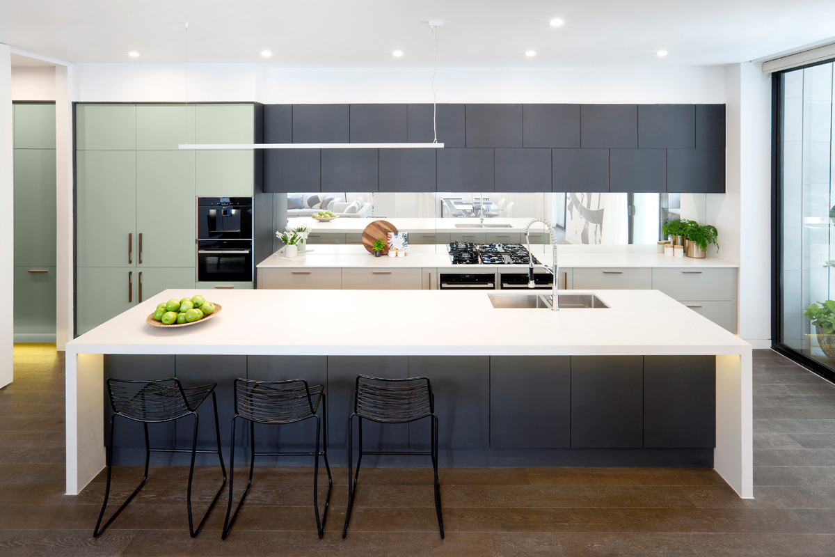 Contempo Twist -  Andy & Ben from The Block have created a modern kitchen with an Art Deco twist fitting the heritage of the building. Colour and texture have been used in interesting and refreshing ways to celebrate Art Deco whilst keeping clean contemporary lines. Top cabinets in Black Riven have been offset to create interest and play on the Deco style and have been paired with Newbury Baye and Bayleaf creating a fresh colour palette. An entertainer's dream, the design features ample storage throughout both the kitchen and sizable butler's pantry, chic NEFF appliances and stunning Caesarstone ® Fresh Concrete benchtops.