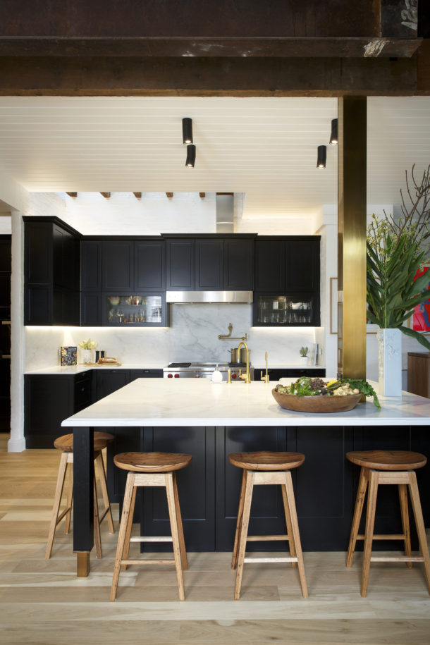 New-Age Shaker  Black is the new white in kitchens – it's the perfect way to put a modern spin on a traditional Shaker-style design. The Sierra cabinets in Matt Black, Caesarstone ® benchtops in Pure White and gold highlights gives a luxe look and contemporary feel without adding a high-end price tag. Designed for a Melbourne family of four, this kitchen needed to be as functional as it is beautiful. The supersized island bench offers plenty of seating, storage, a place for appliances as well as a secret hiding zone for the two young boys of the house with the centre of the island! A butler's pantry and laundry adds additional storage and workspace to this busy kitchen.