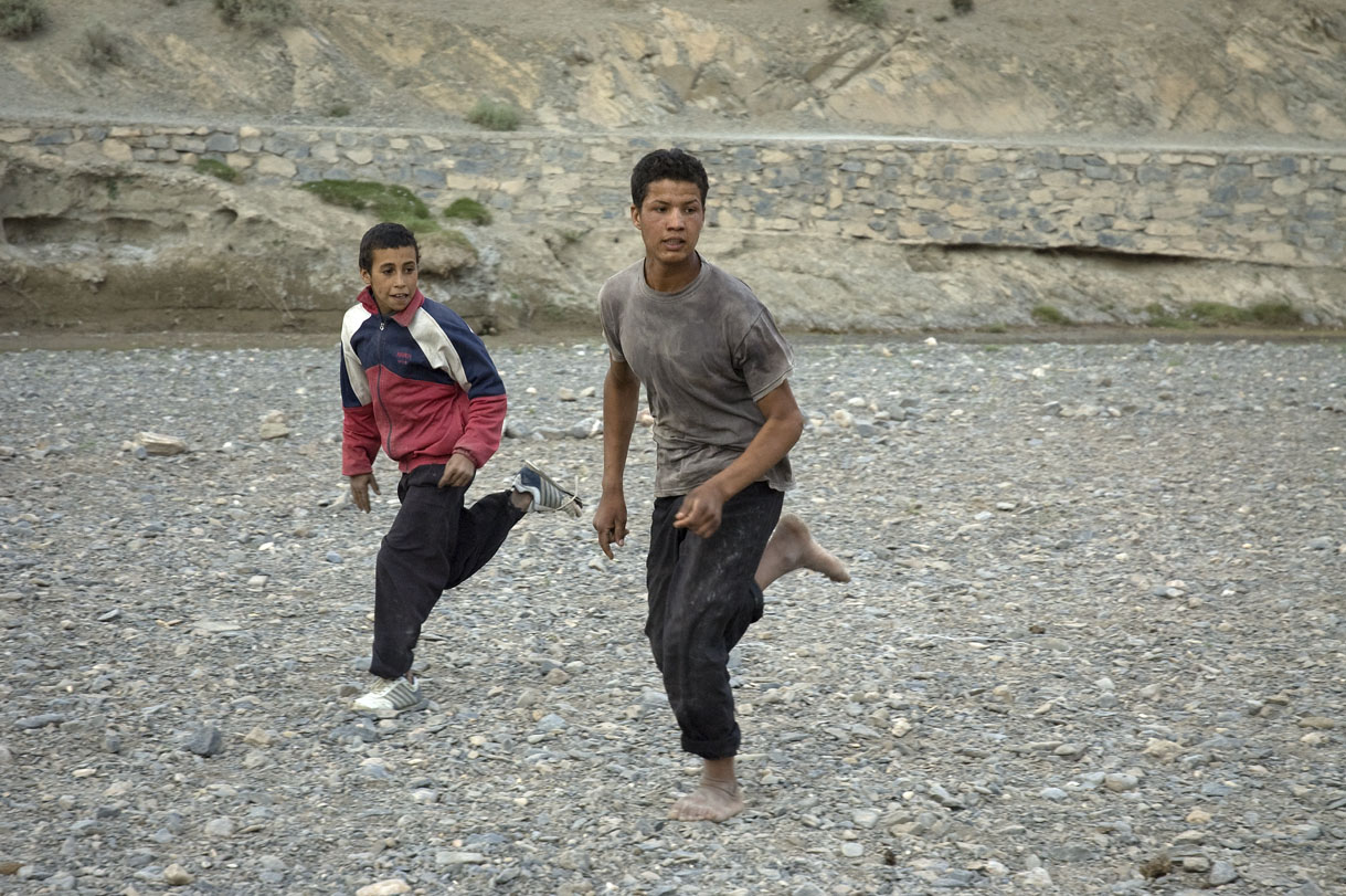 Playing soccer on the dry river bed.