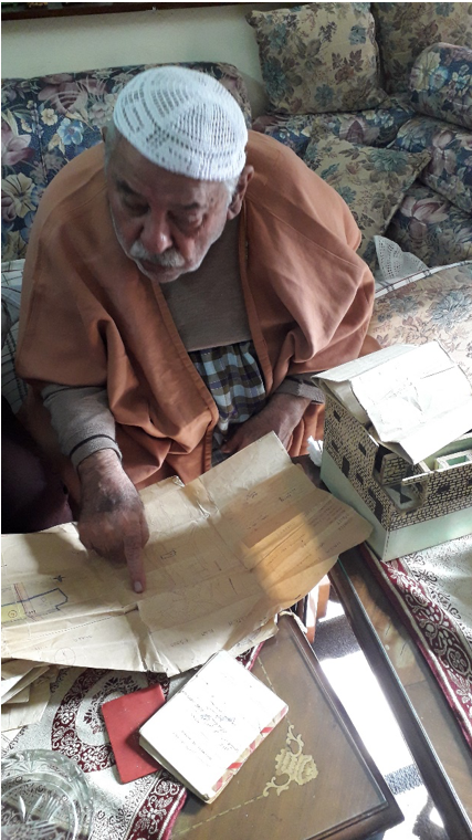 83 year-old Yehya Fawzi Abu Hishmeh points to the plans of the home he was forced to flee as a 12-year old boy in 1948.