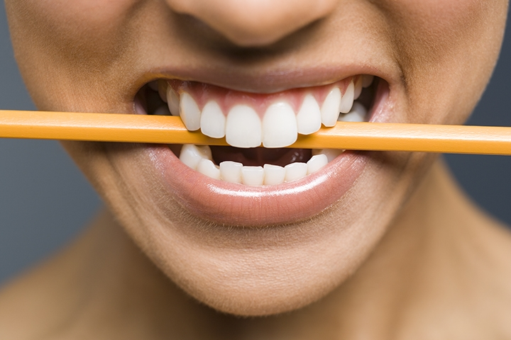 Try holding a pencil loosely between your teeth while you sing