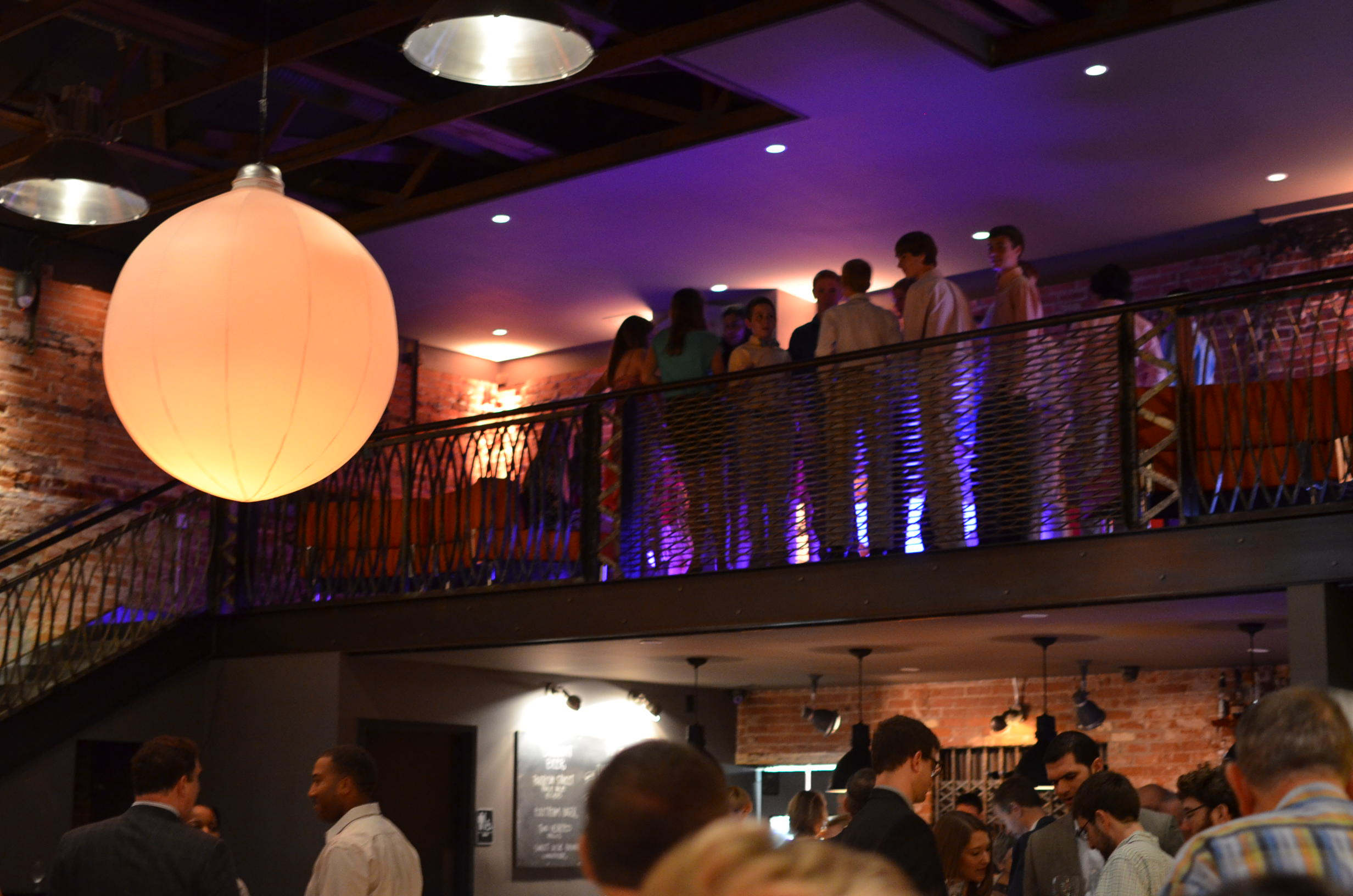 Guests overlook the Front Room from the mezzanine
