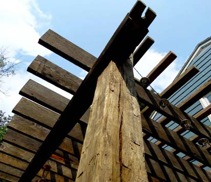 A pergola of reclaimed rafters and beams adds personality to your backyard.