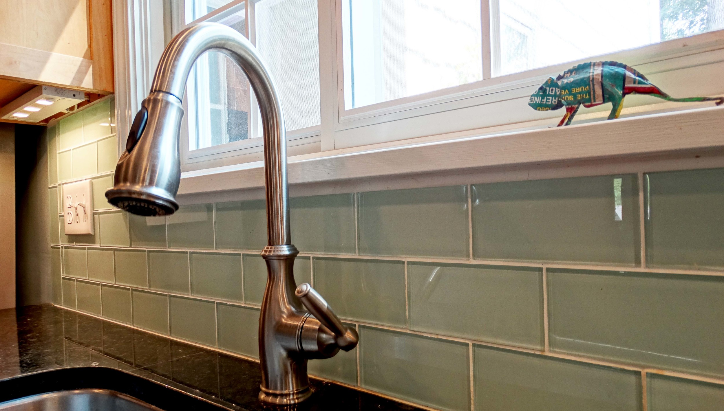 Retro glass subway tiles and under counter lighting blend modern and old school touches in this reimagined kitchen.