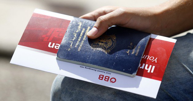 Image: A migrant holds his passport and a train ticket in Freilassing, Germany September 15, 2015. REUTERS/Dominic Ebenbichler