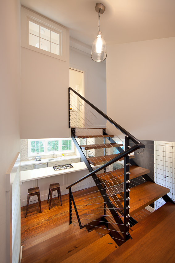 Floating stairs with steel and cable rail leading from second level to basement.