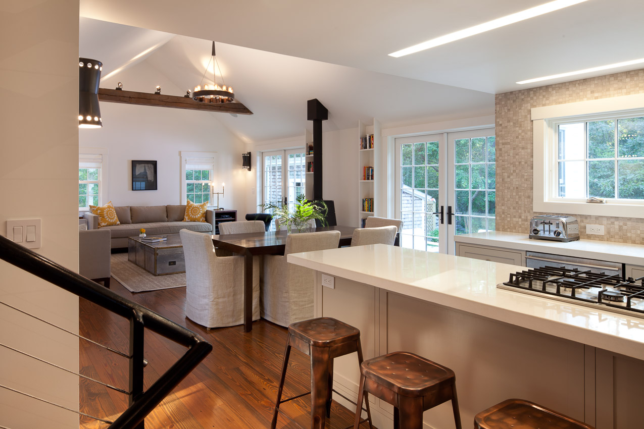 View of kitchen, dining and living room in parsonage, including concrete kitchen countertop.