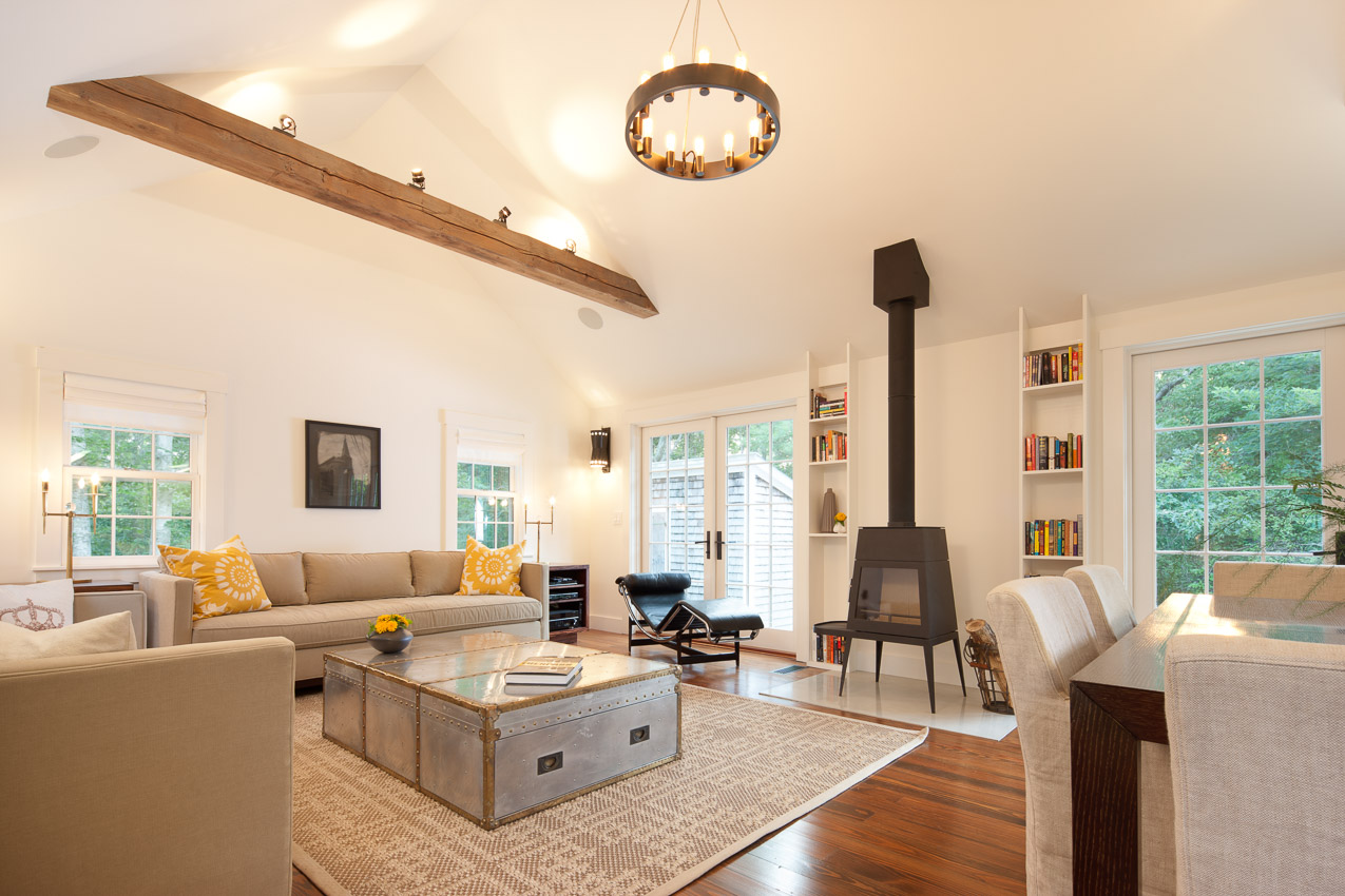 Living room perfectly blends the old and the new with reclaimed wood beam and modern woodstove set on a marble inlay.