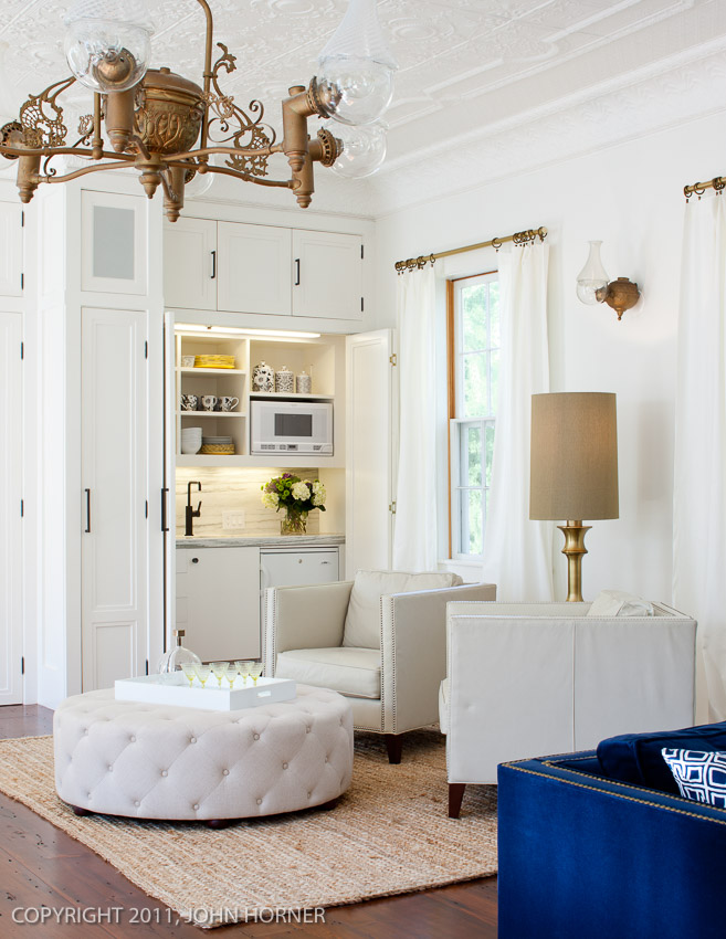 Original converted gaslight fixture with matching sconce and kitchenette, hidden behind bi-fold doors.