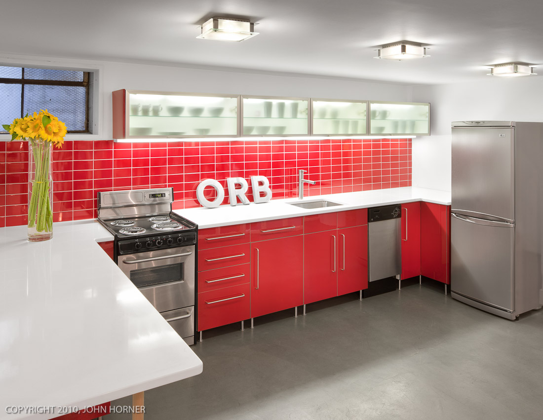 Kitchen in office loft building with tile backsplash, Silestone counter and poured concrete floor.