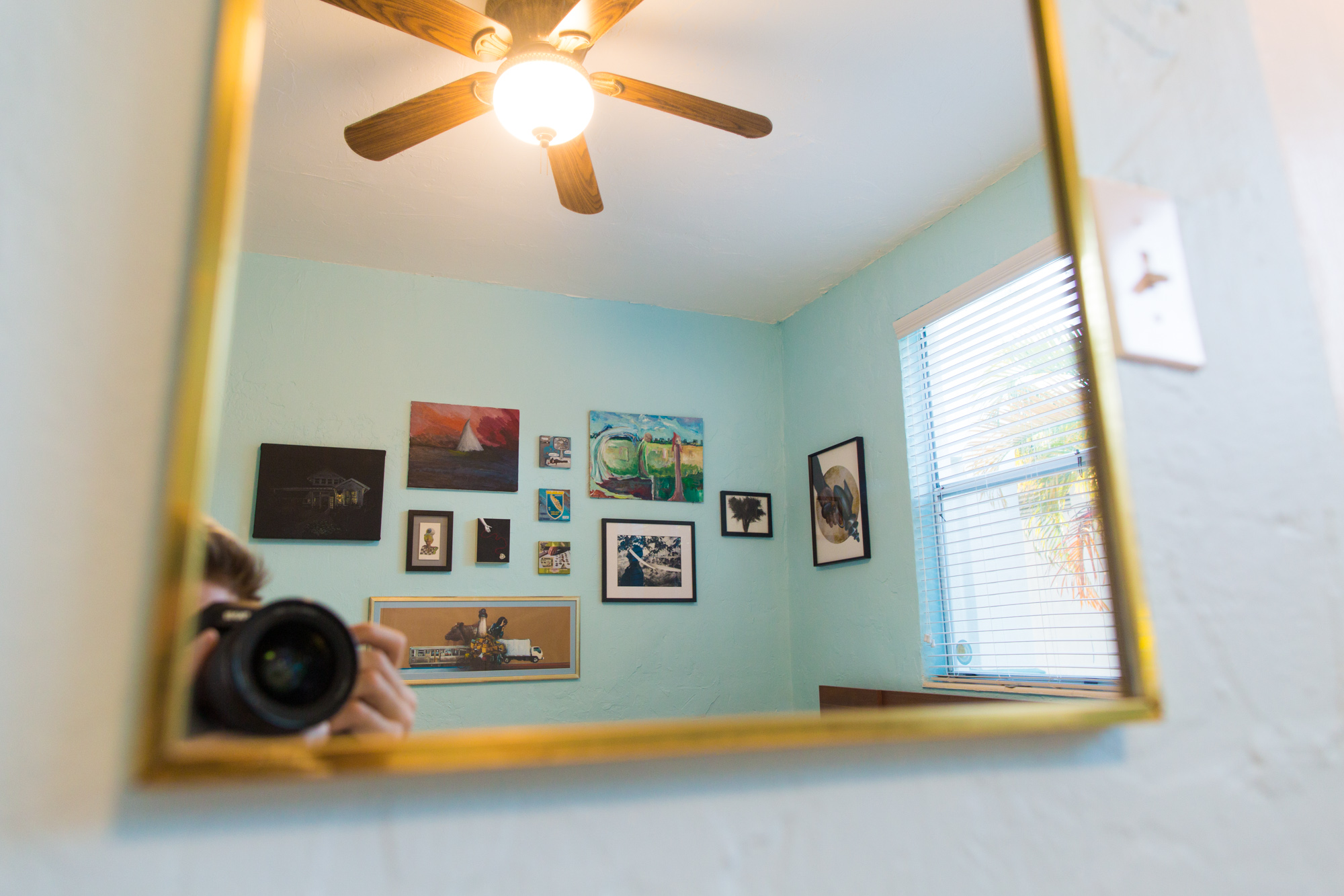 Salon wall of artwork reflected in bedroom mirror