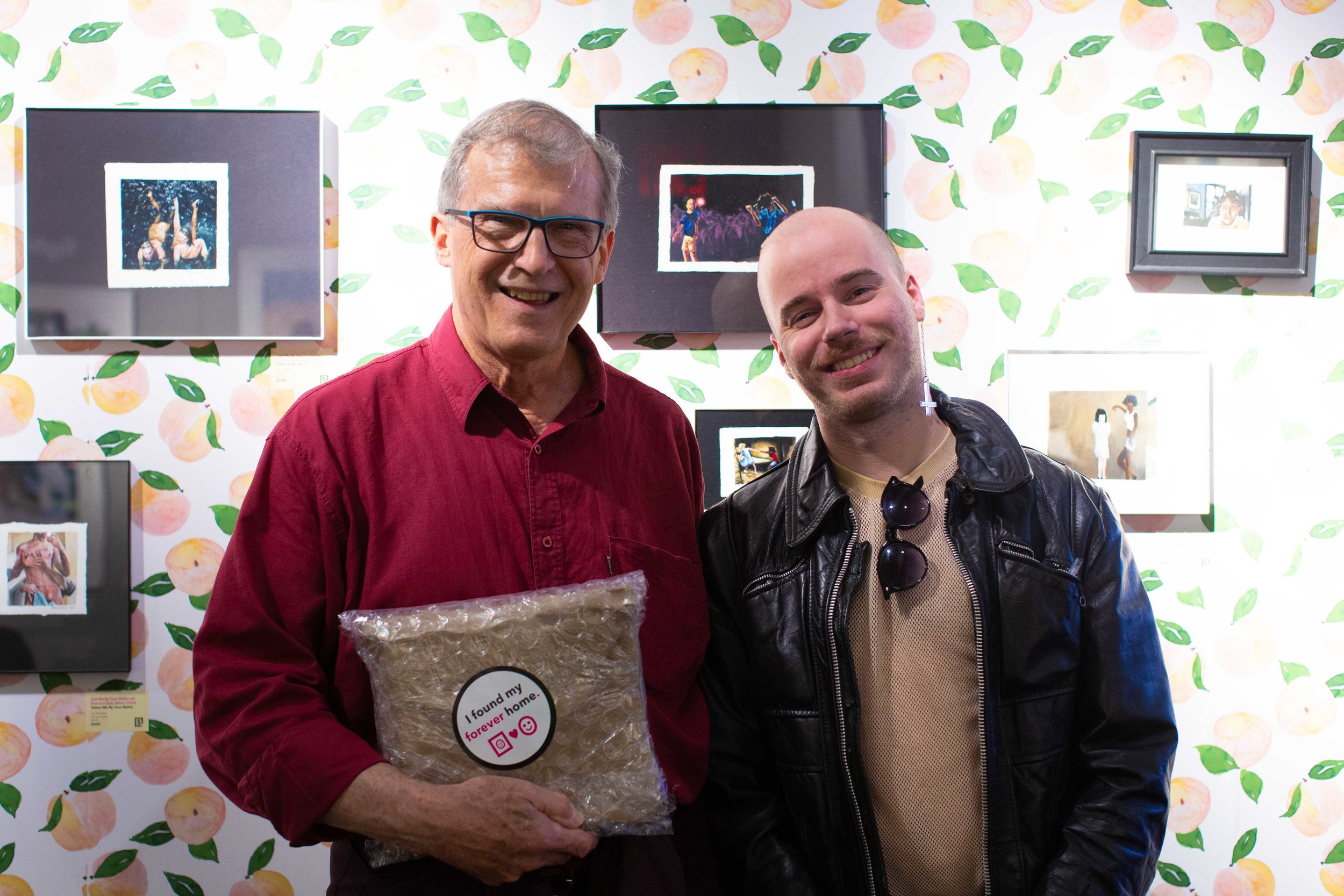 """Above: Adam Chuck poses with a new collector in front of his """"Call Me By Your Preferred Pronoun"""" installation at Superfine! Art Fair in NYC, May 2019."""