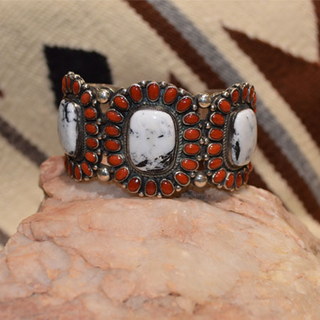 Above is a unique cuff bracelet with three large White Buffalo pieces set inside a cluster of red coral. Made by Navajo artist Calvin Martinez.