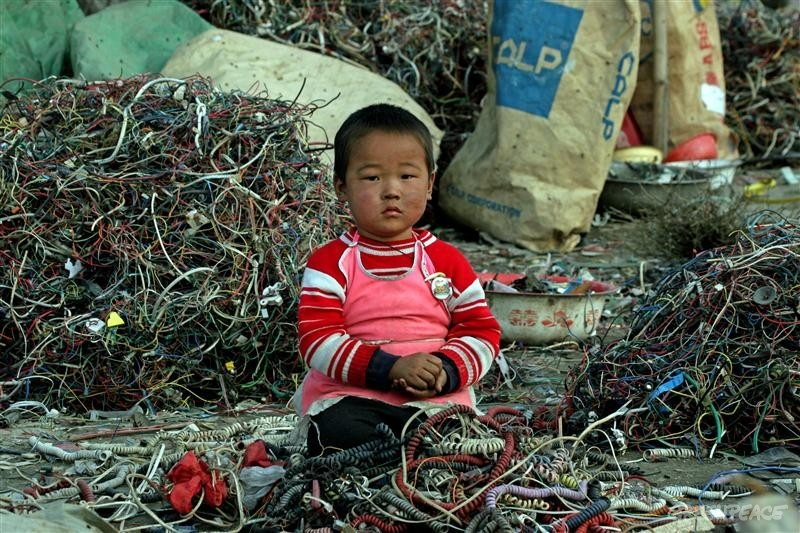 A child sits among discarded wires in Guiyu, China.                    (www.greenpeace.org)