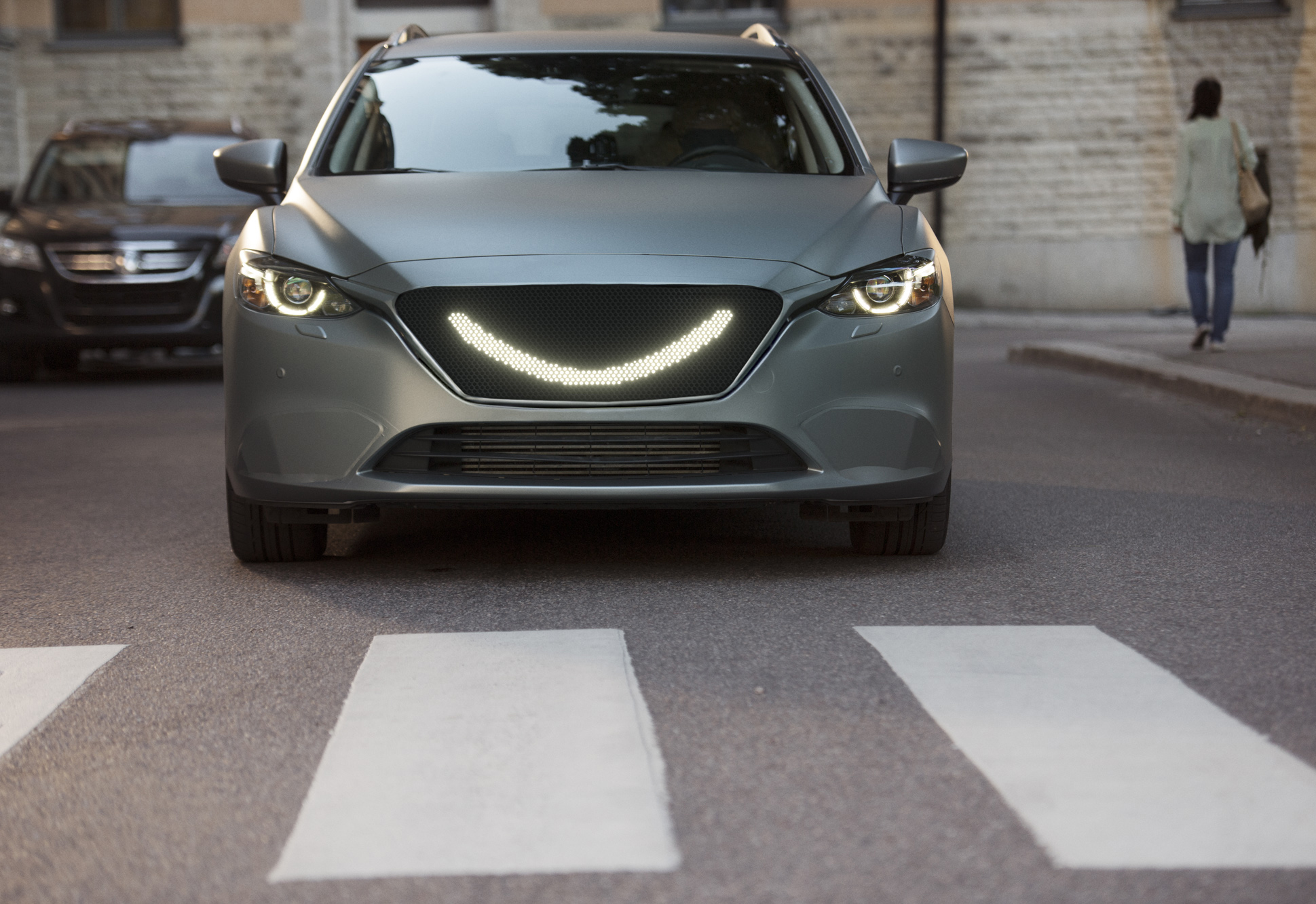 07 - When the self-driving car's sensors detect a pedestrian a smile lights up at the front of the car and the car stops.jpg