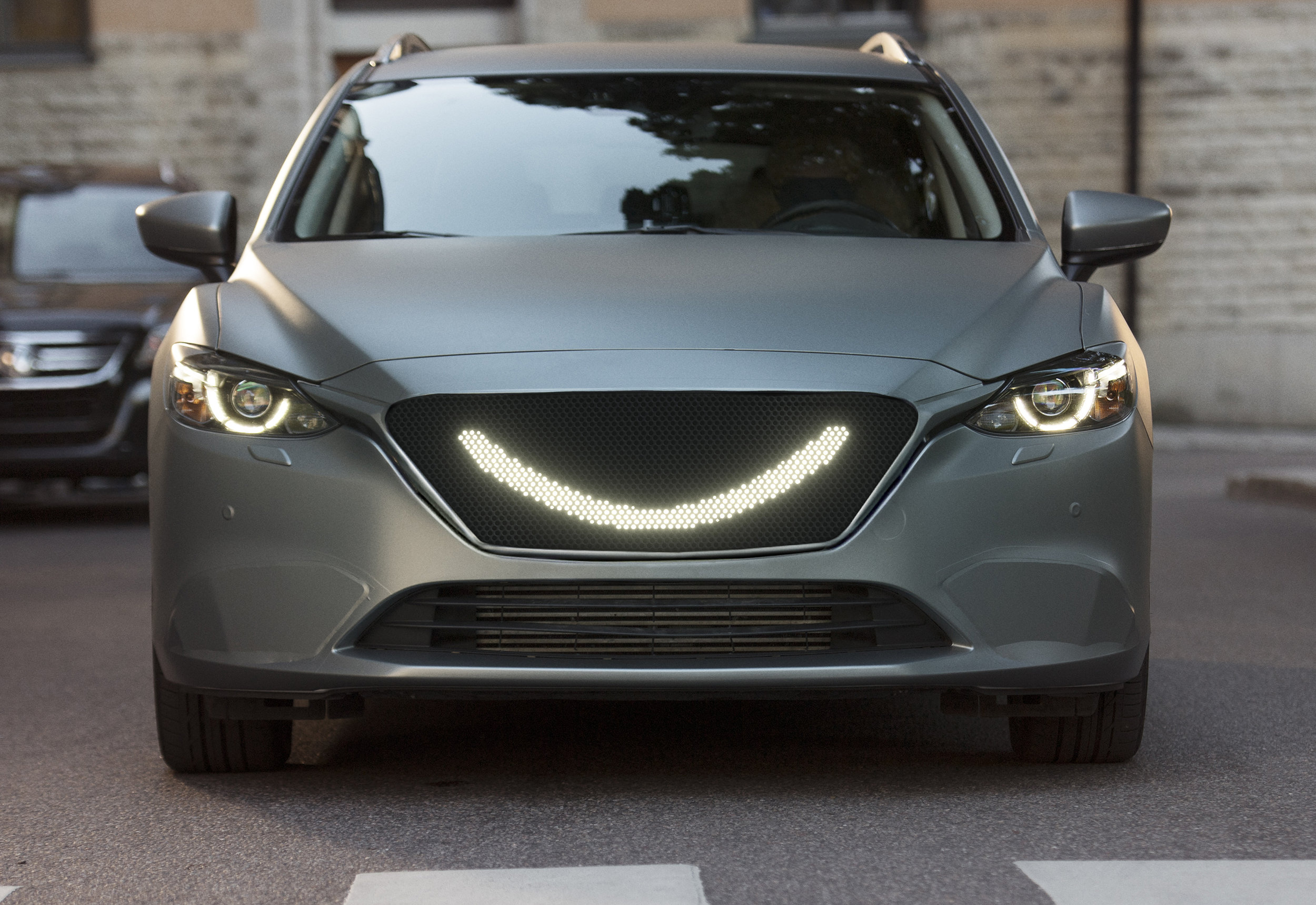 When the self-driving car's sensors detect a pedestrian a smile lights up at the front of the car and the car stops.jpg