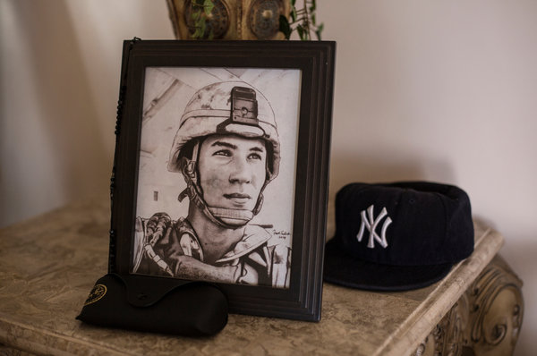 """A portrait of Lance Cpl. Gregory Buckley Jr. in his family's home in Oceanside, N.Y. He was shot to death in 2012 by a teenage """"tea boy"""" living on his base in Helmand Province."""
