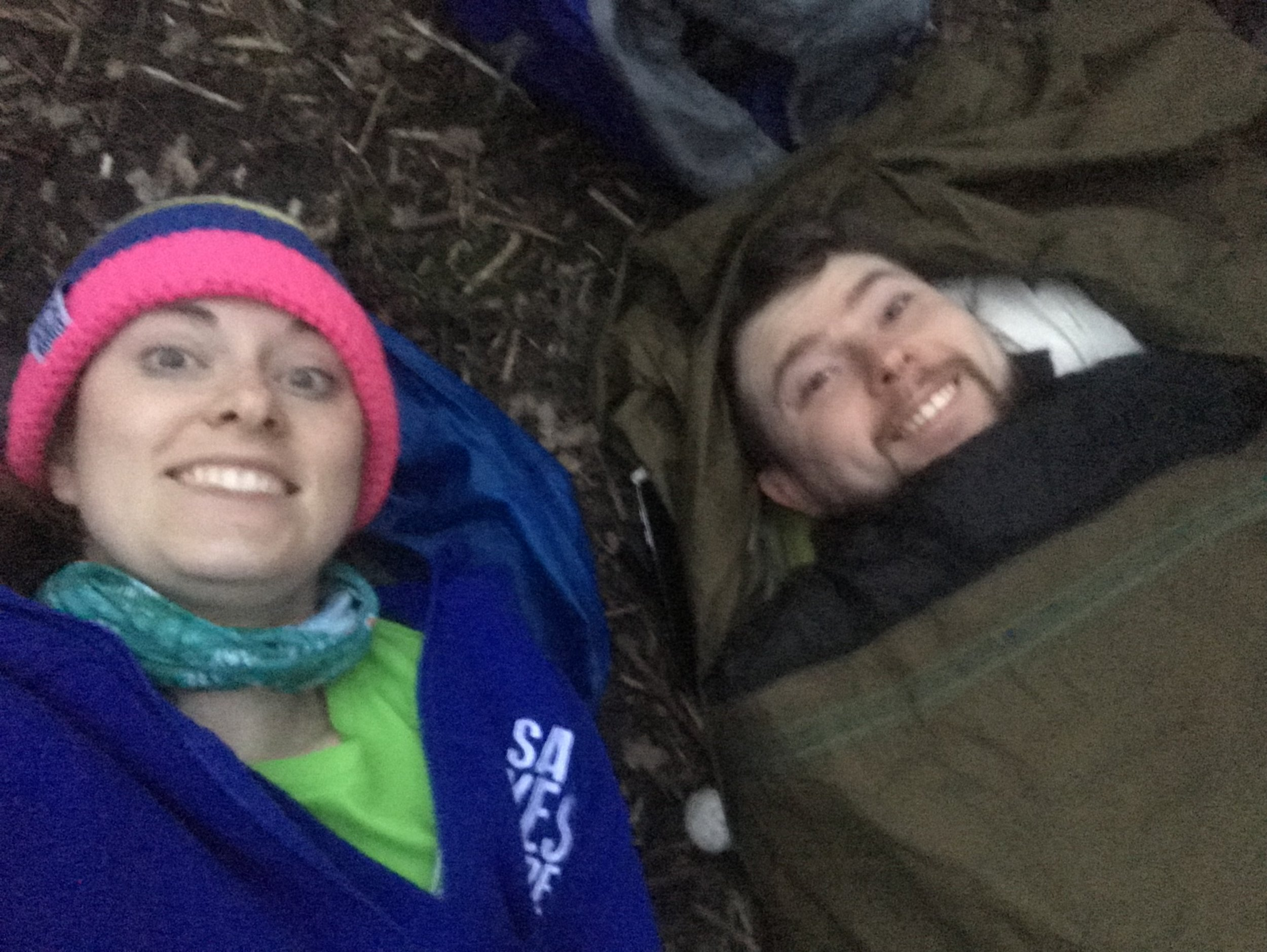 A photo of Jen and Ian in their sleeping bags bivvying in the woods