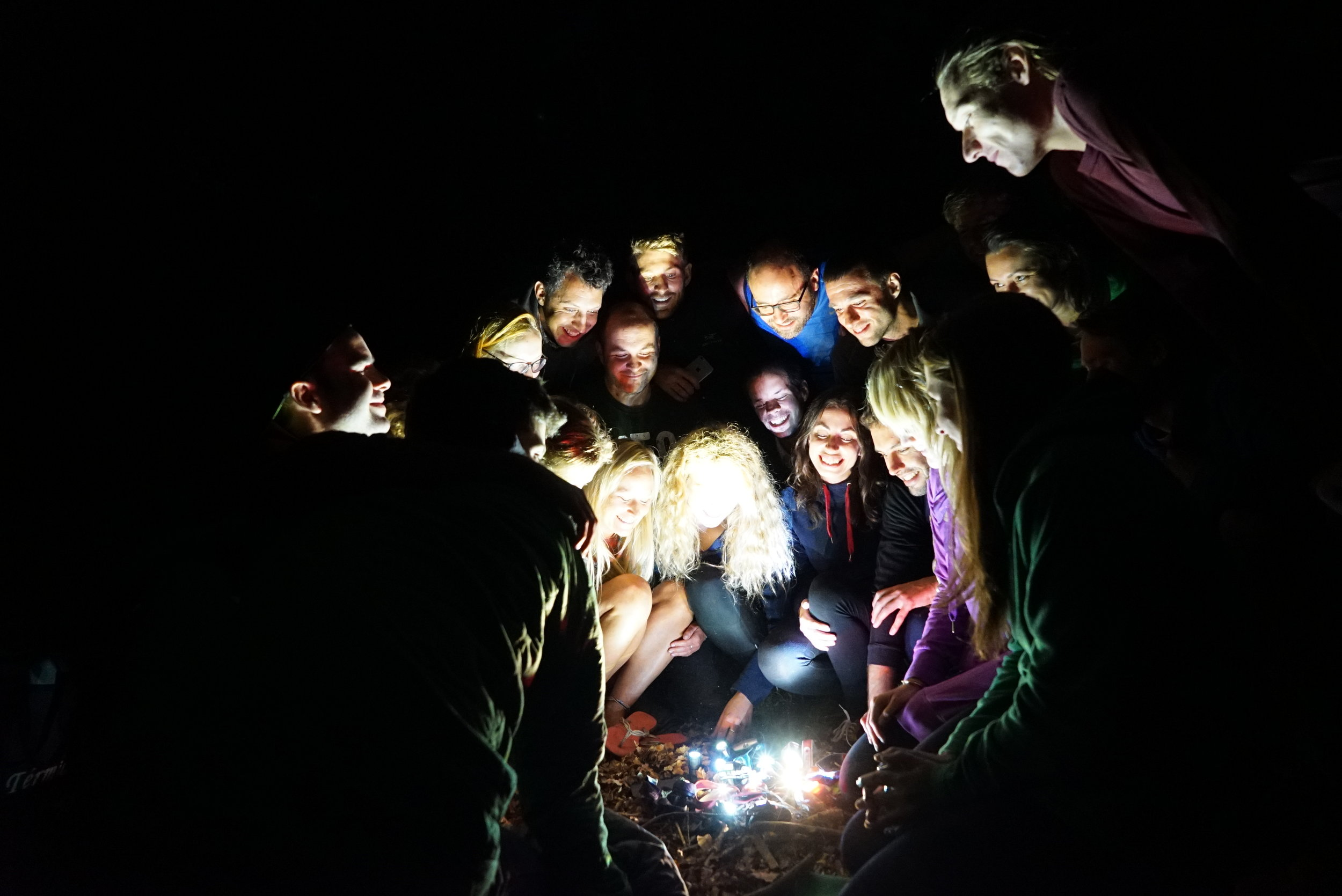 A group of people on a wild camp surrounding a pile of headtorches on the ground, which look a bit like a campfire!