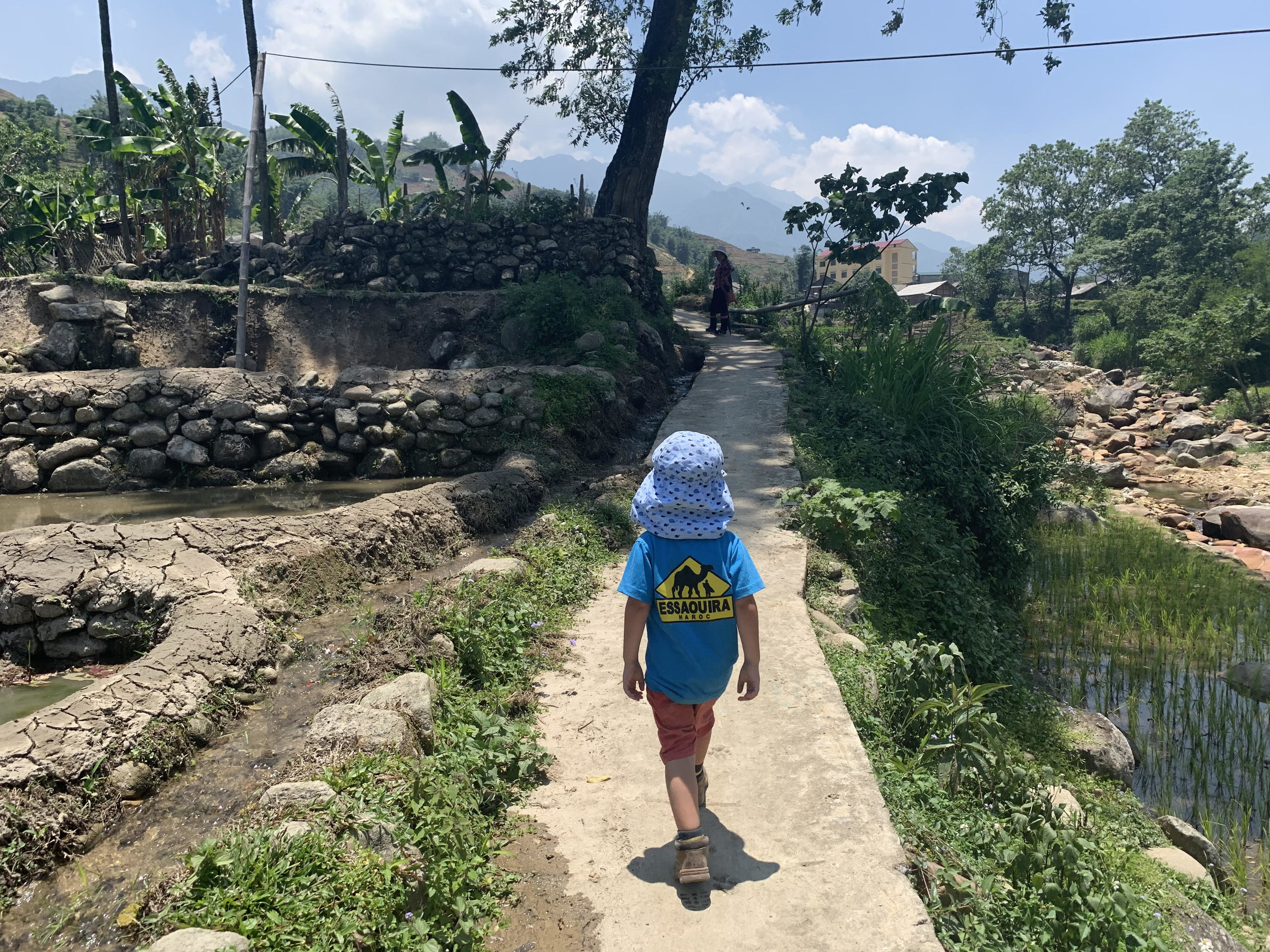 3-year old Sam walks along a narrow path with mountains in the distance