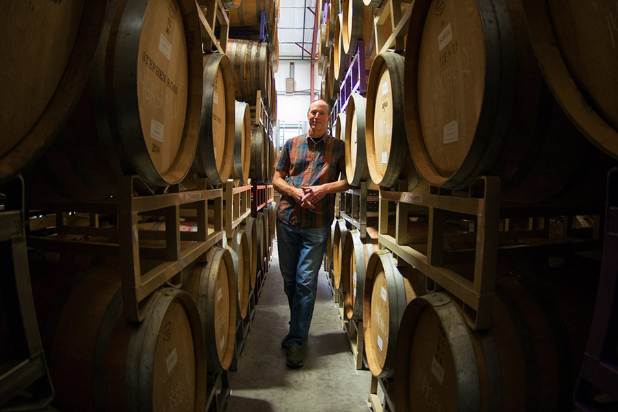Winemaker Stephen Dooley between rows of stacked barrels.