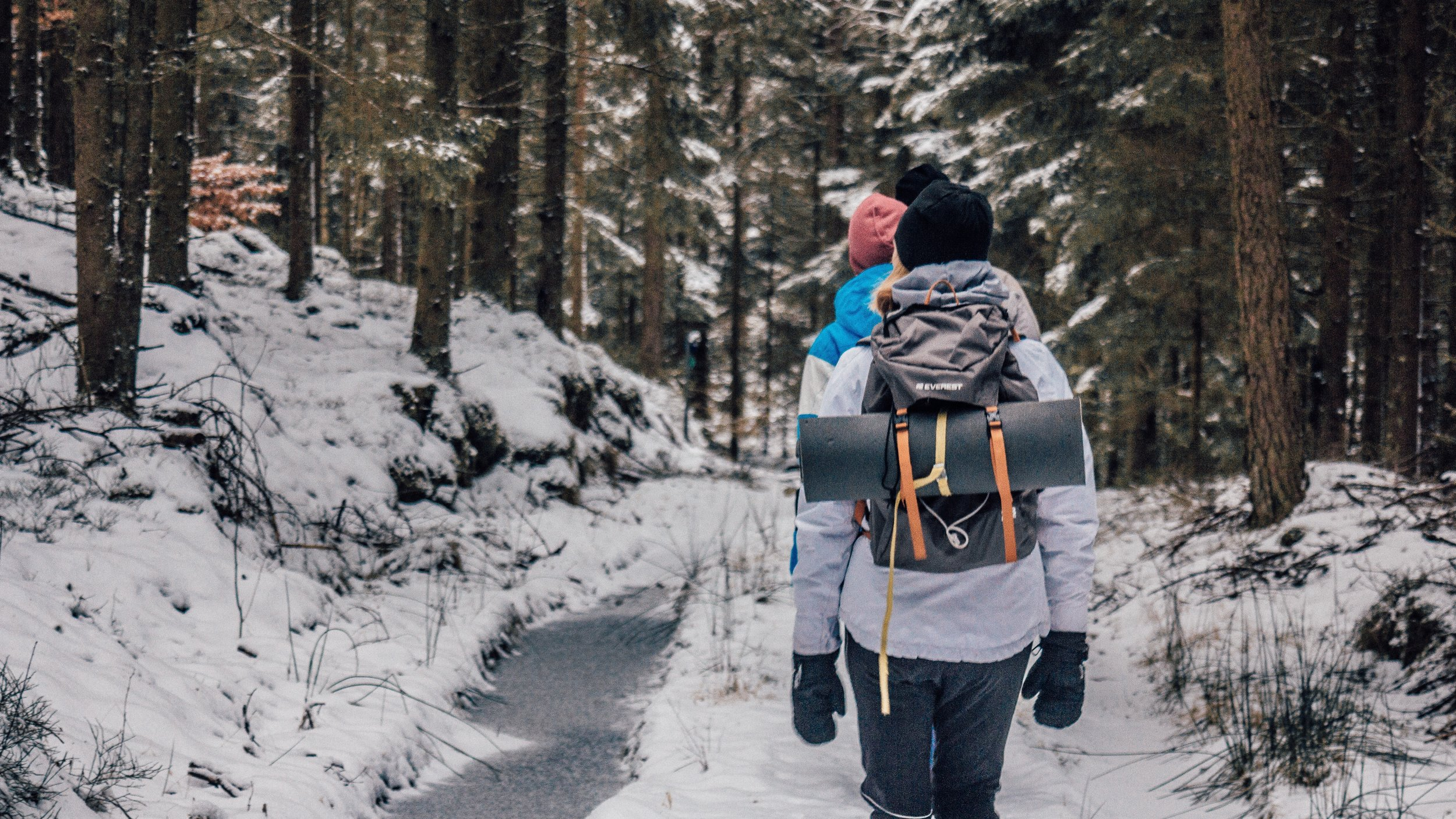 group of people hiking in the snow during winter near a stream