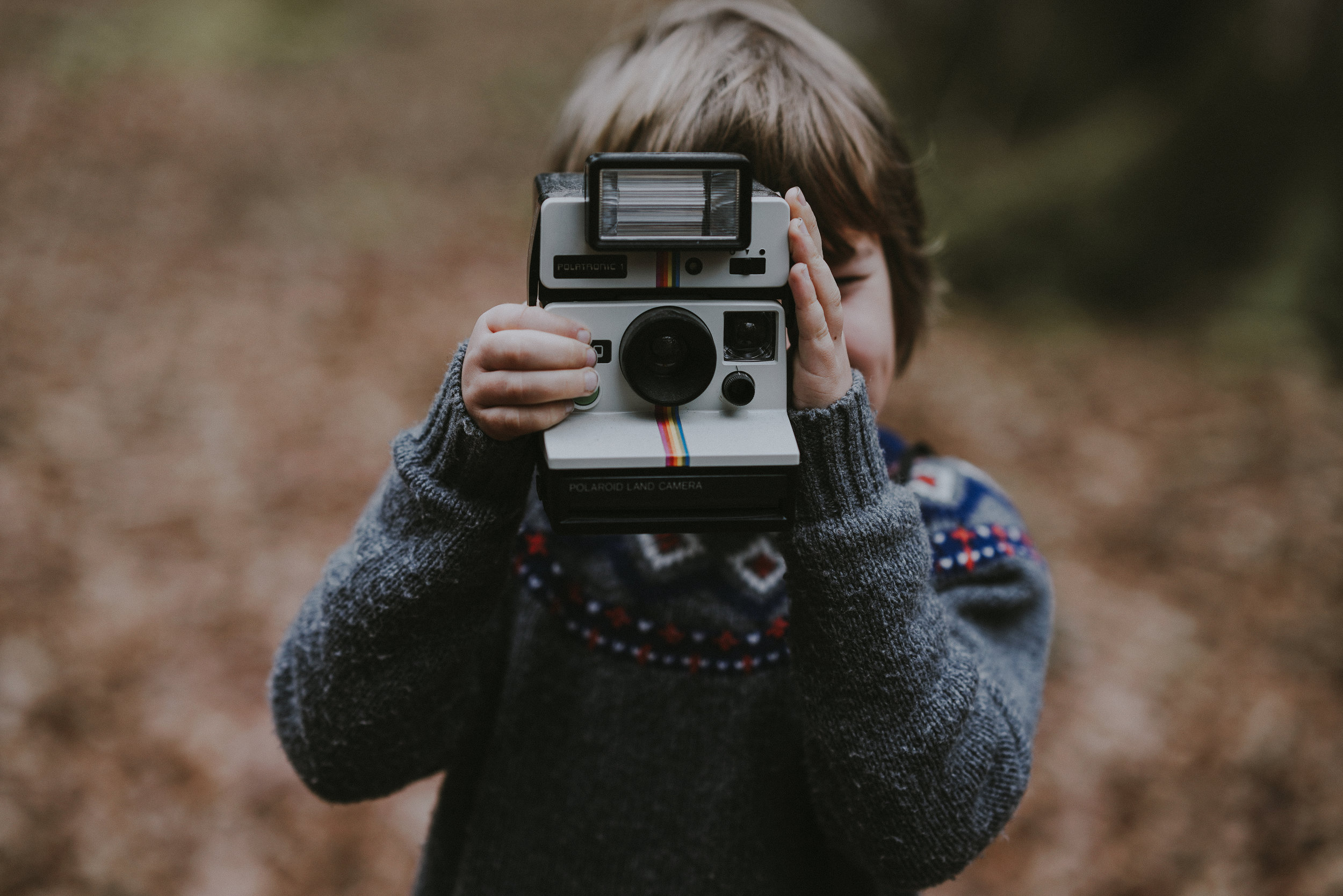 child taking a photo in the woods